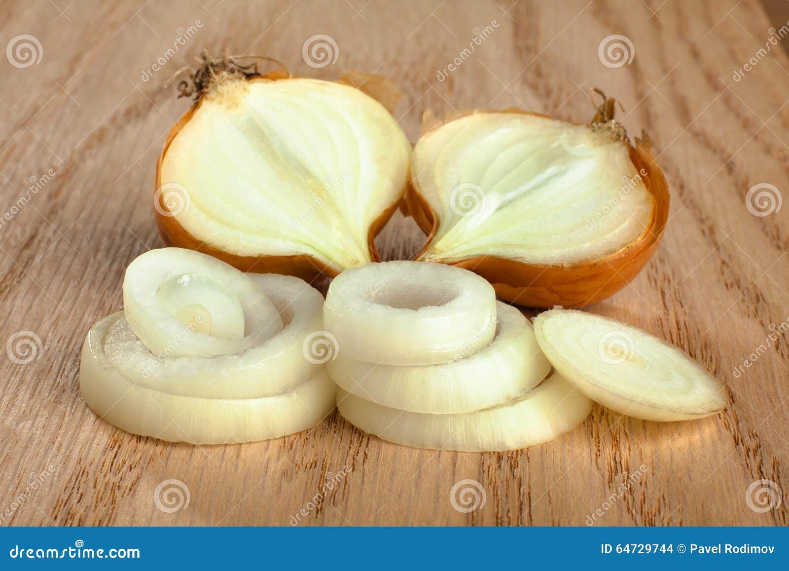 Cipolle affettate fresche su fondo di legno