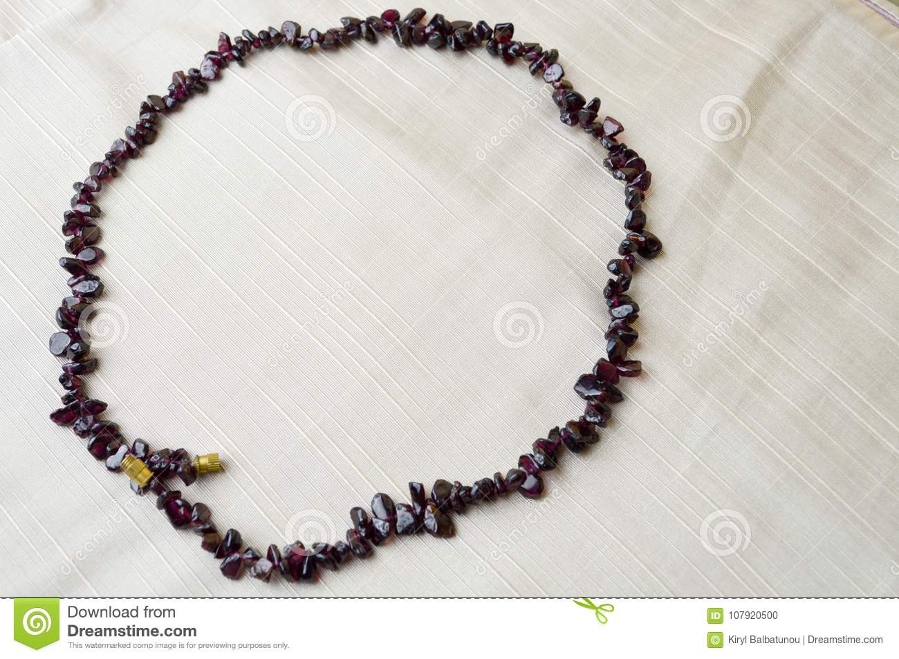 The circle is made of female beautiful beads, necklaces of brown dark stones, amber with a background of beige fabric