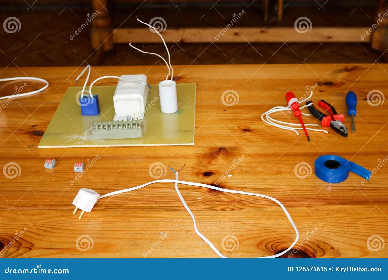 Circuito elettrico con i cavi ed i pezzi di ricambio, attrezzatura dell installazione, pinze, nastro elettrico blu, cacciaviti su