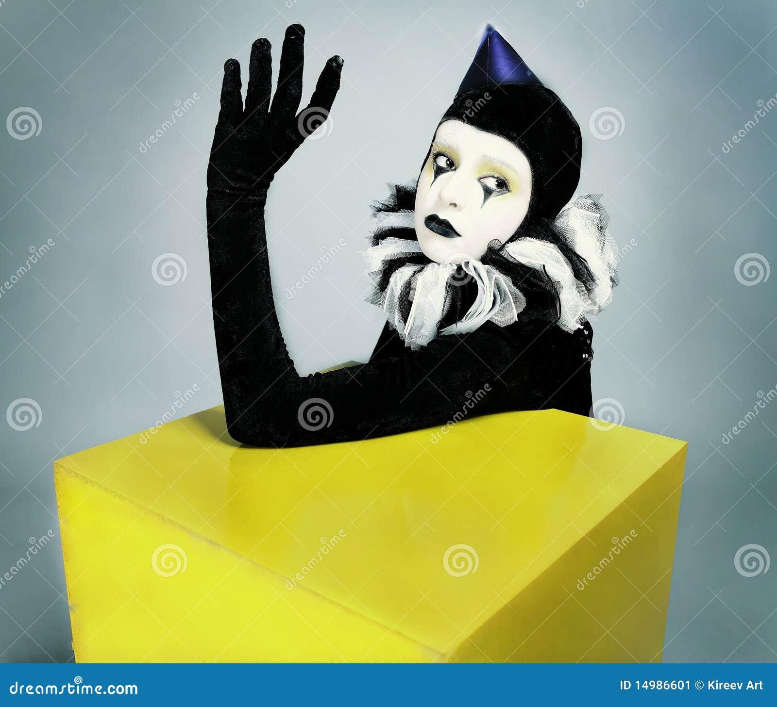 Circus fashion mime posing near a yellow square
