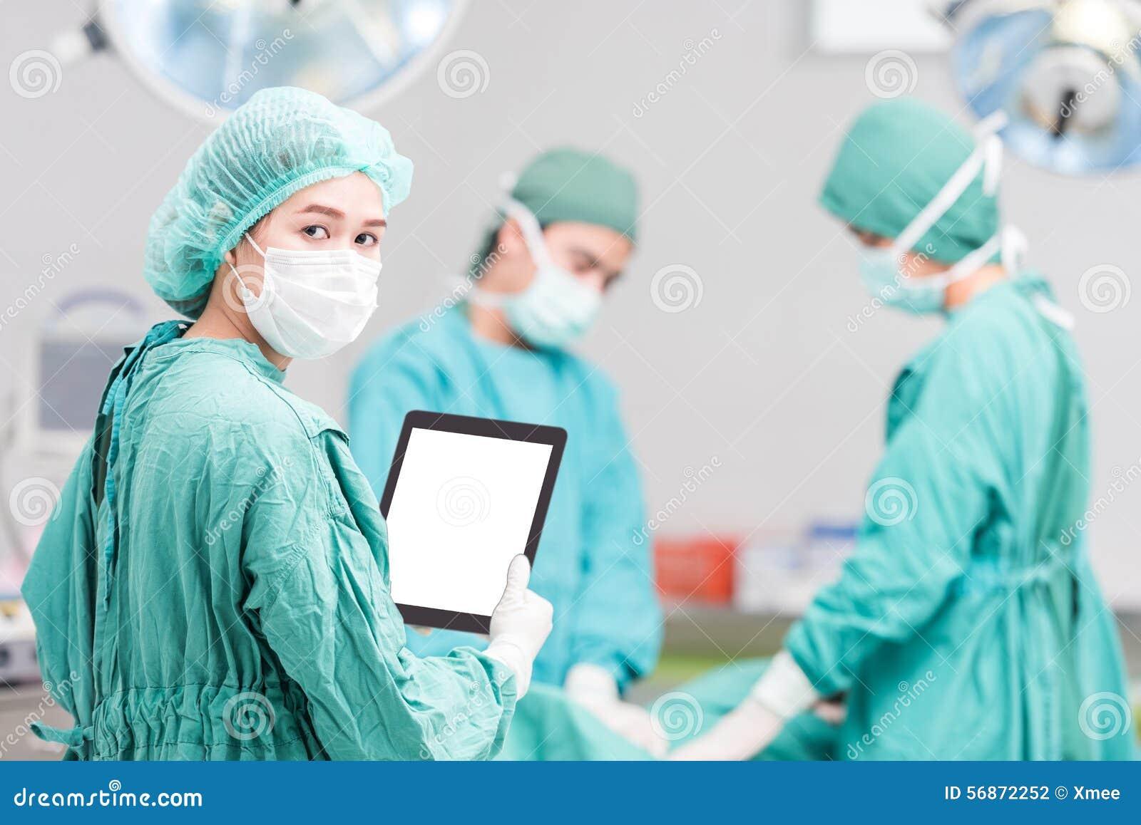 Cirujano de sexo femenino joven del doctor de la enfermera de la mujer que usa la tableta