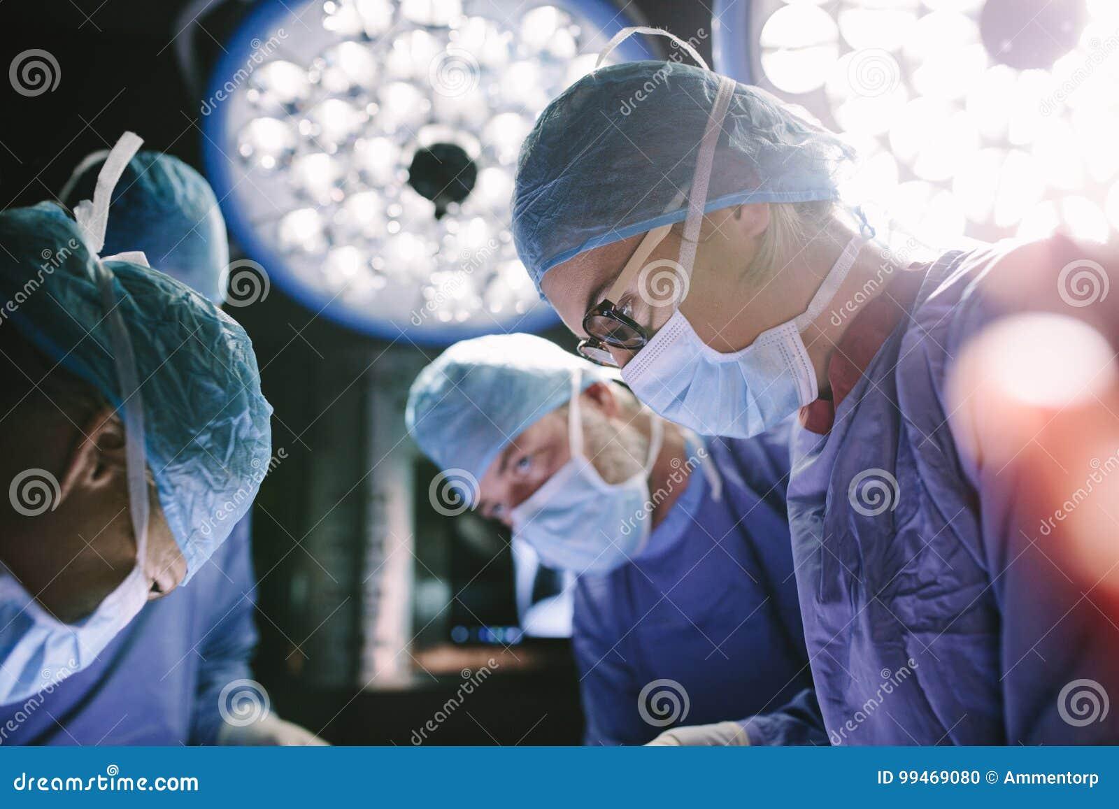 Cirurgião concentrado que executa a cirurgia com sua equipe