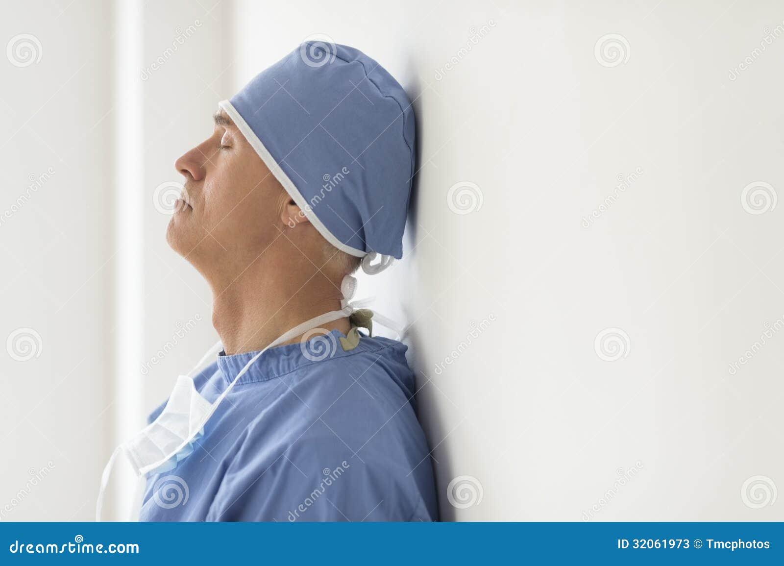 Cirurgião With Eyes Closed que inclina-se na parede em Ho