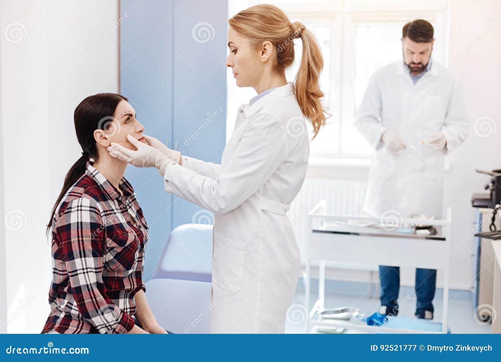 Cirurgião plástico agradável que guarda sua cara dos pacientes