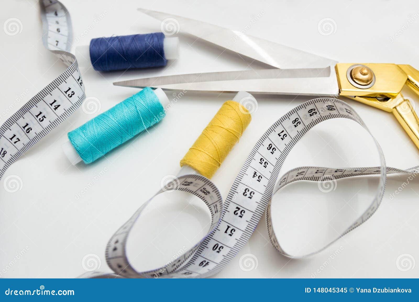 Ciseaux d or, fils bleus, bleus et jaunes, bande de mesure se trouvant sur un fond blanc, un ensemble pour couper et couture
