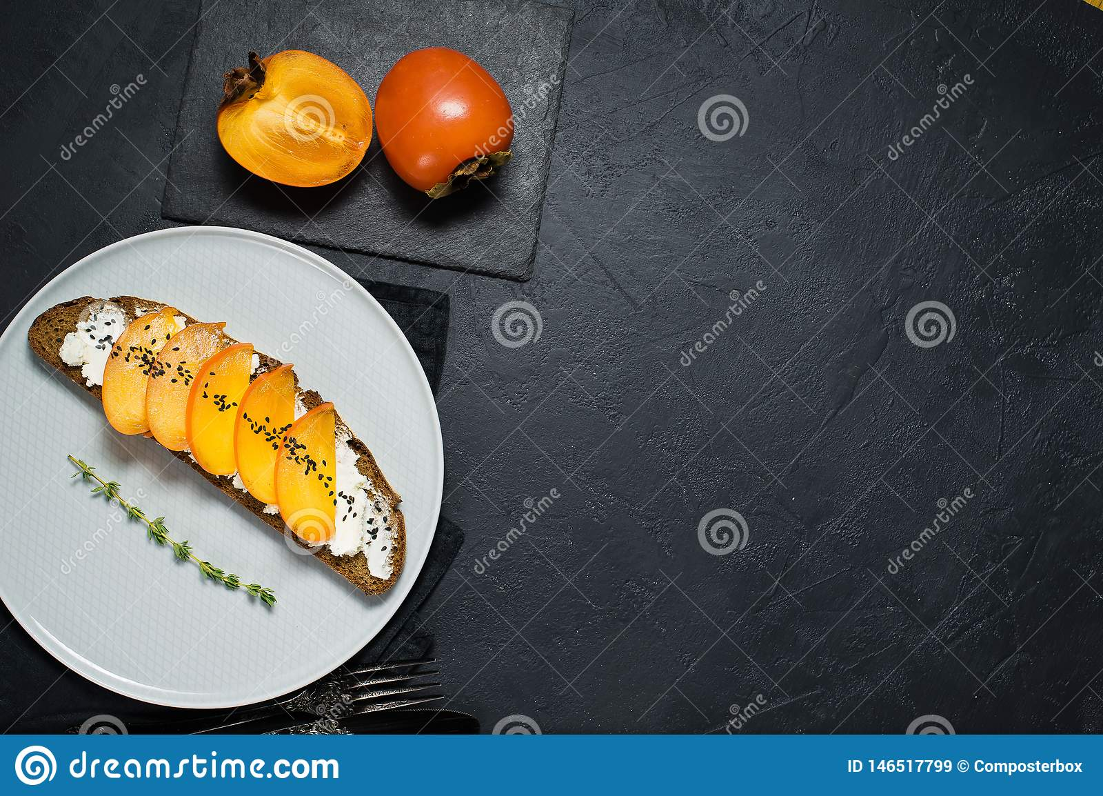 ?ciska z persimmon i mi?kkim serem na czarnym tle z przestrzeni? dla teksta