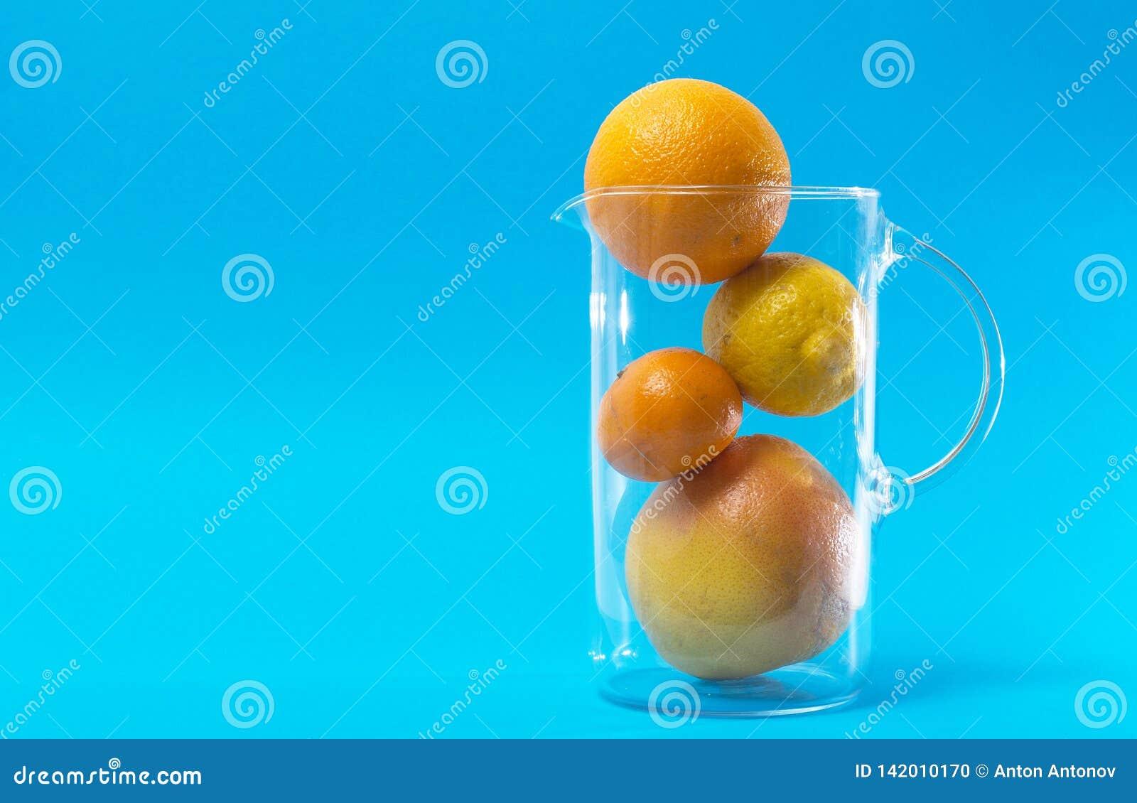 Citrinas frescas Limão, mandarino, toranja e laranja Frutos nos produtos vidreiros no fundo azul