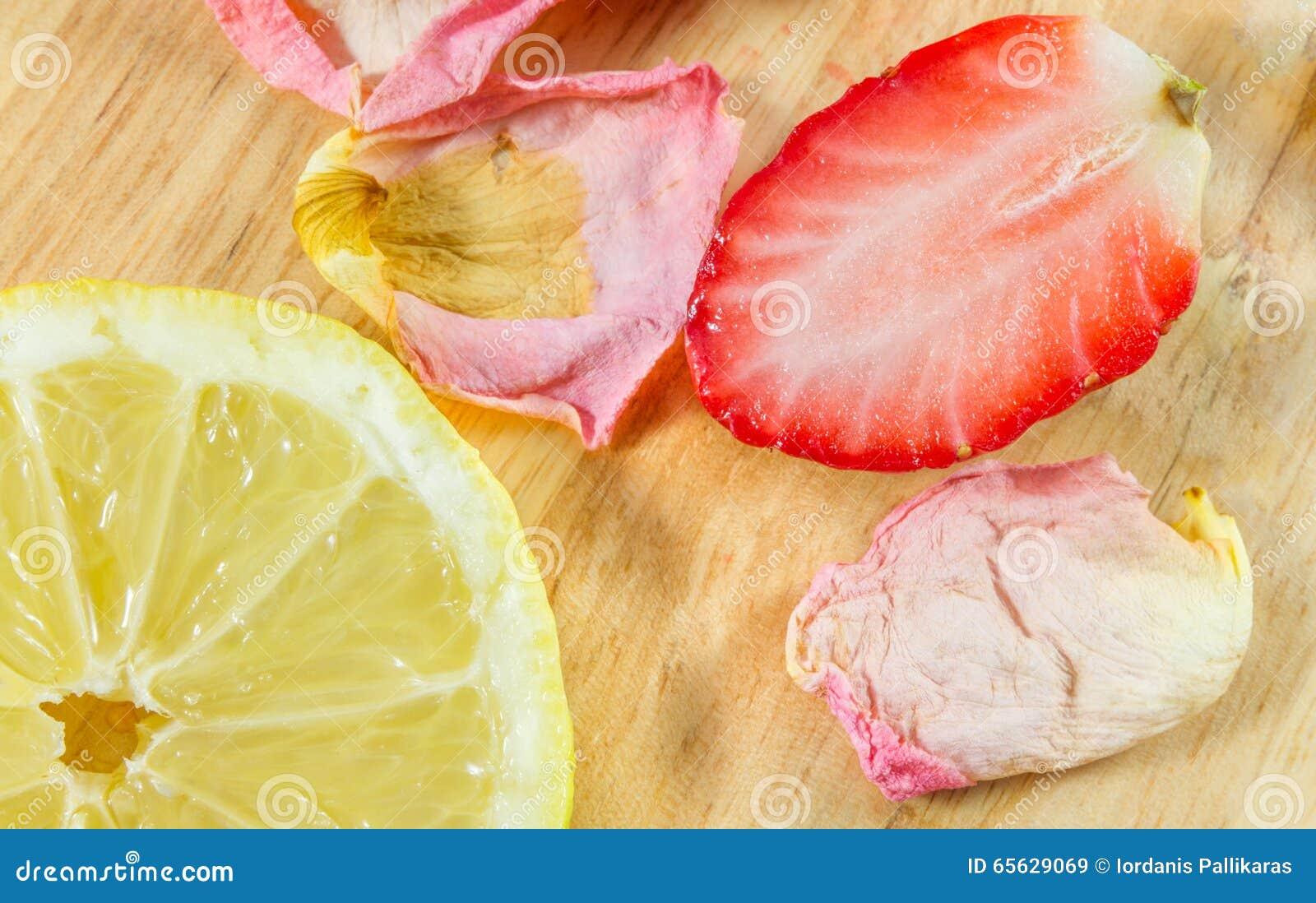 Citron, fraise et pétales de rose coupés en tranches sur le conseil en bois