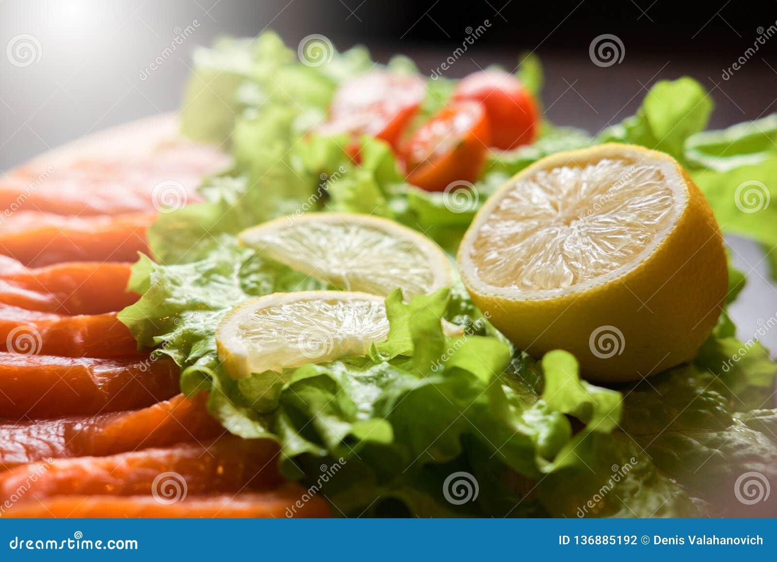 Citron med den röda fisken och sallad och körsbärsröda plockare