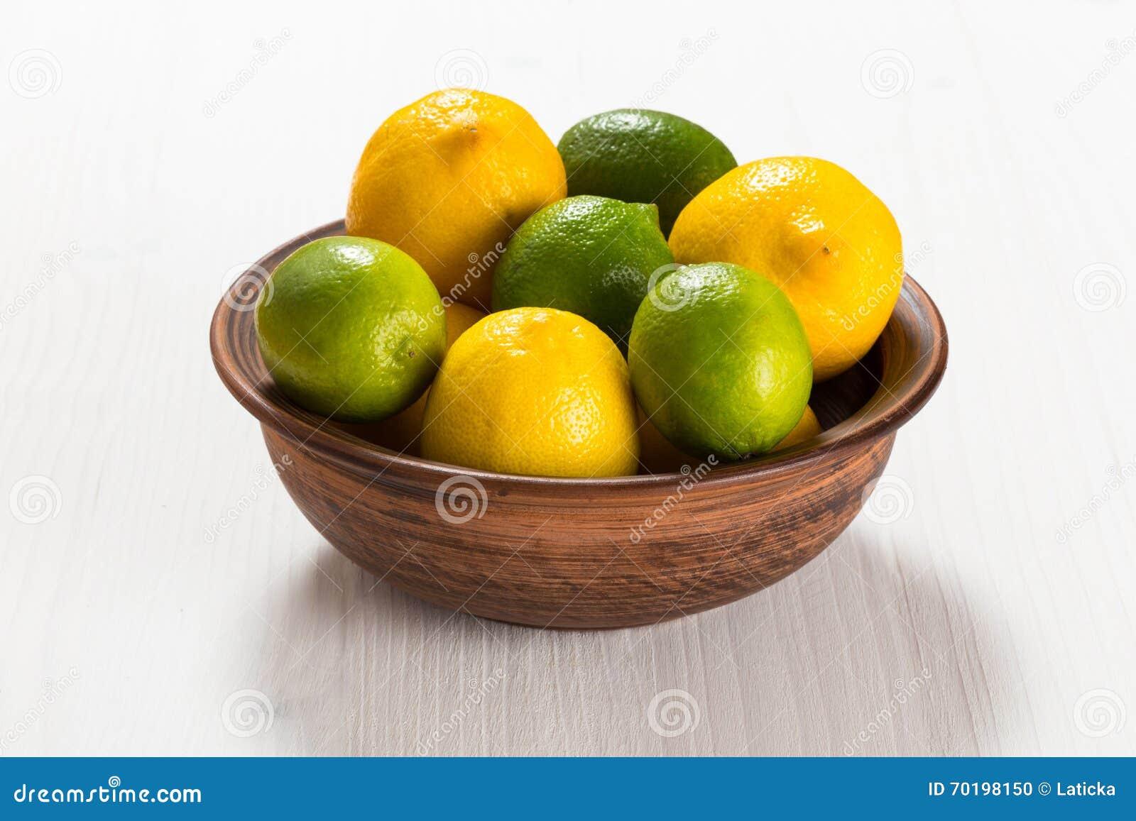Citroner och limefrukter i en lerabunke
