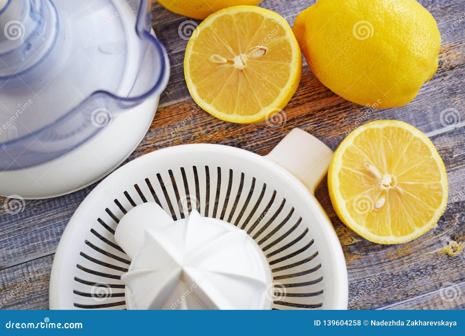 Citrons et presse-fruits frais d agrume sur le fond en bois