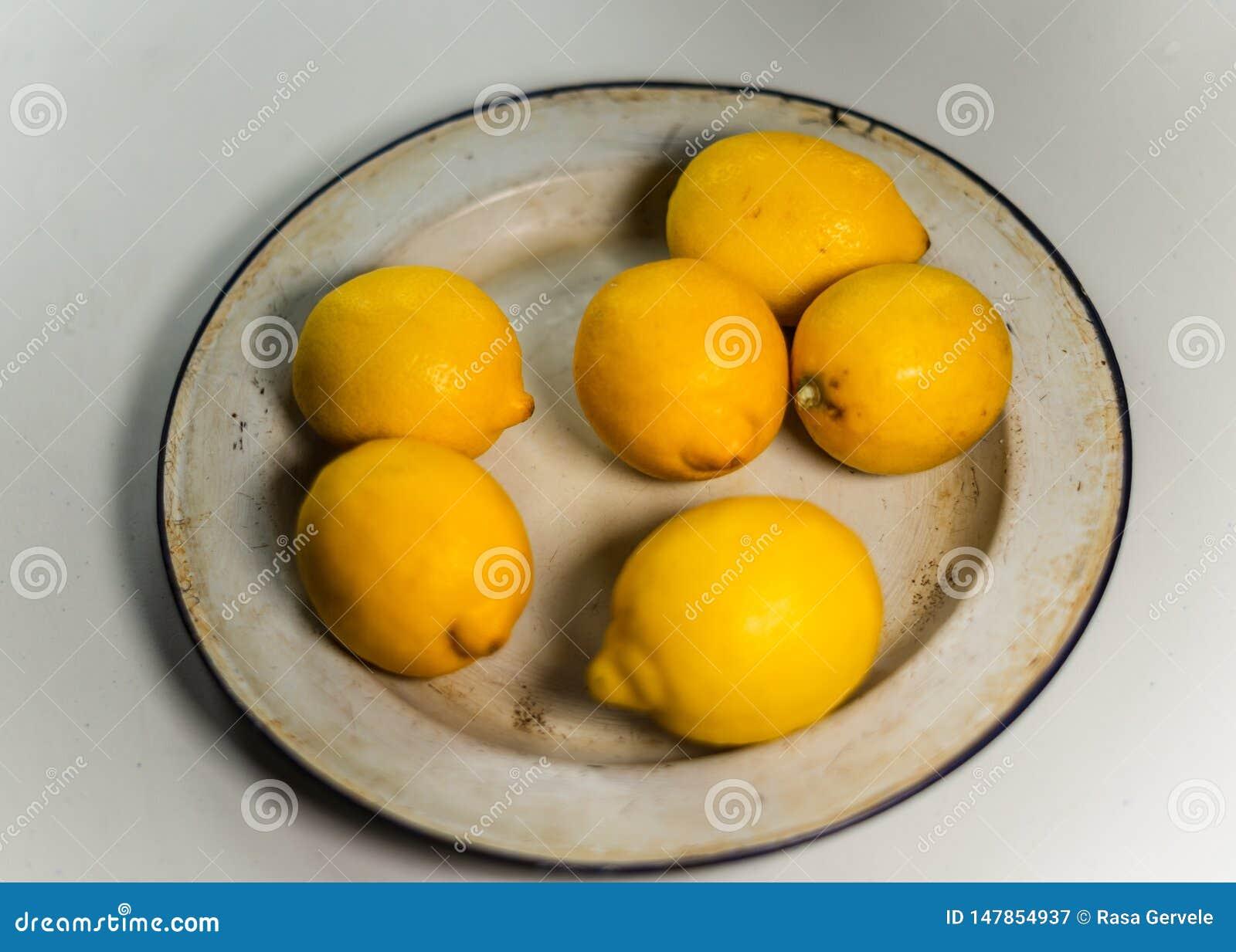Citrons jaunes frais dans le plat d ?mail de cru Fin vers le haut