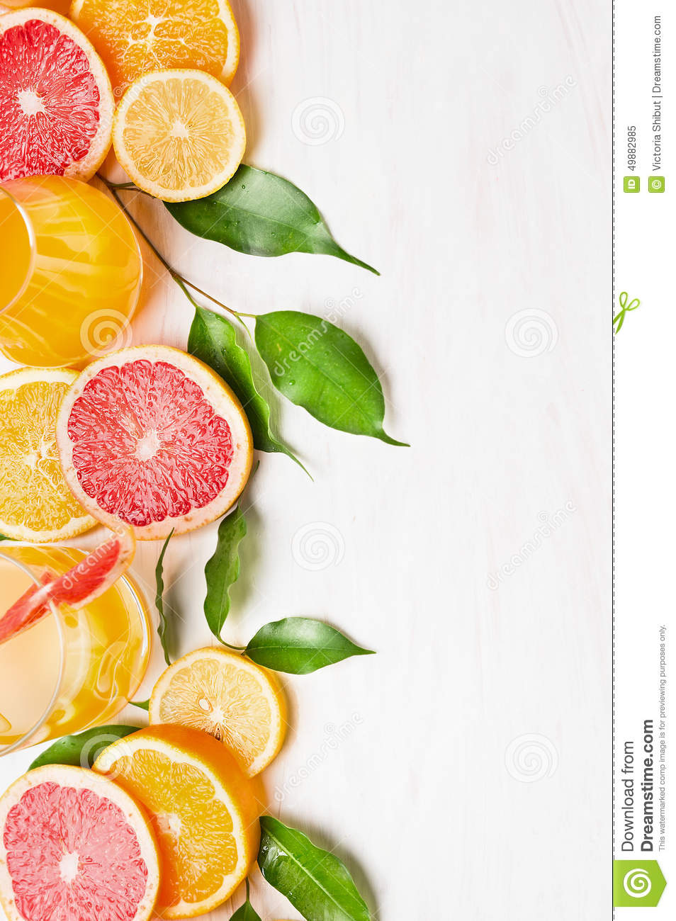 Citrus fruits with green leaves and glass with juice on white wooden table , frame