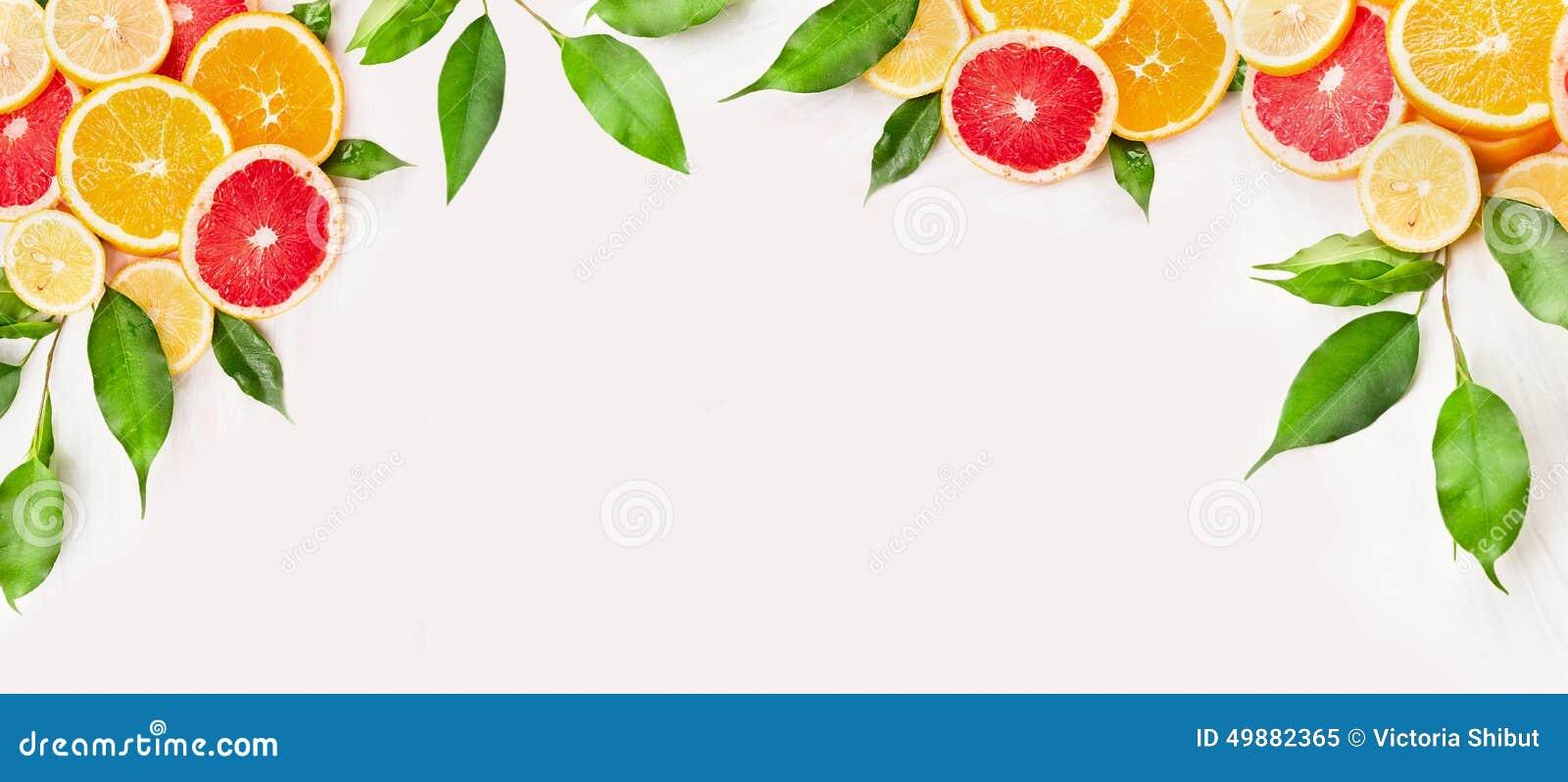 Citrusfrukter skivar med gröna sidor på vit träbakgrund, baner
