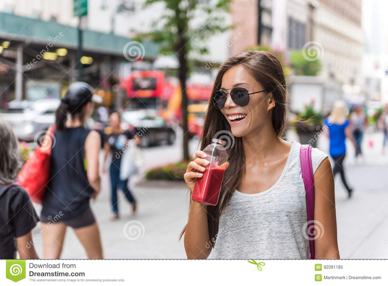 City lifestyle woman drinking healthy fruit juice