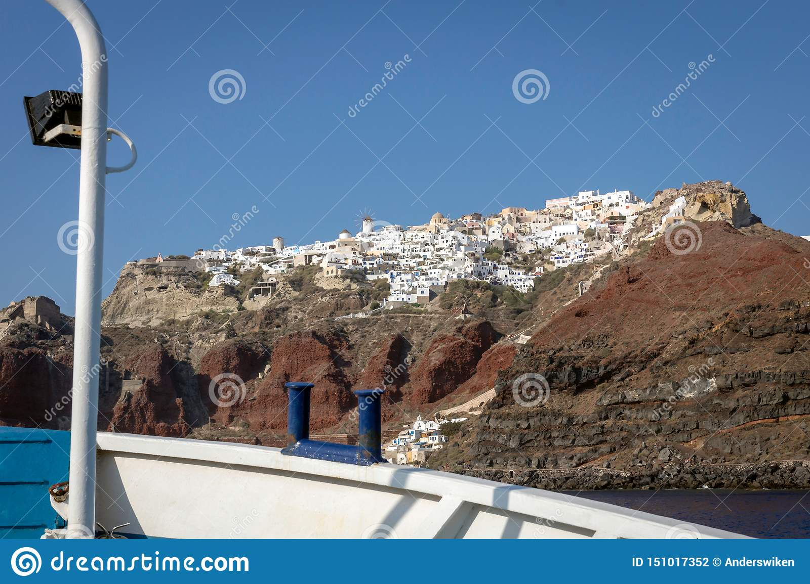 The city of Oia seen from the water in a fishing boat.