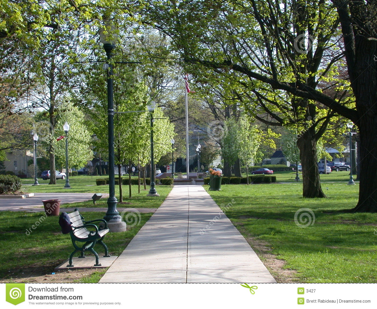 Springtime in a city park in Anytown, USA. Path lined with old-style ...