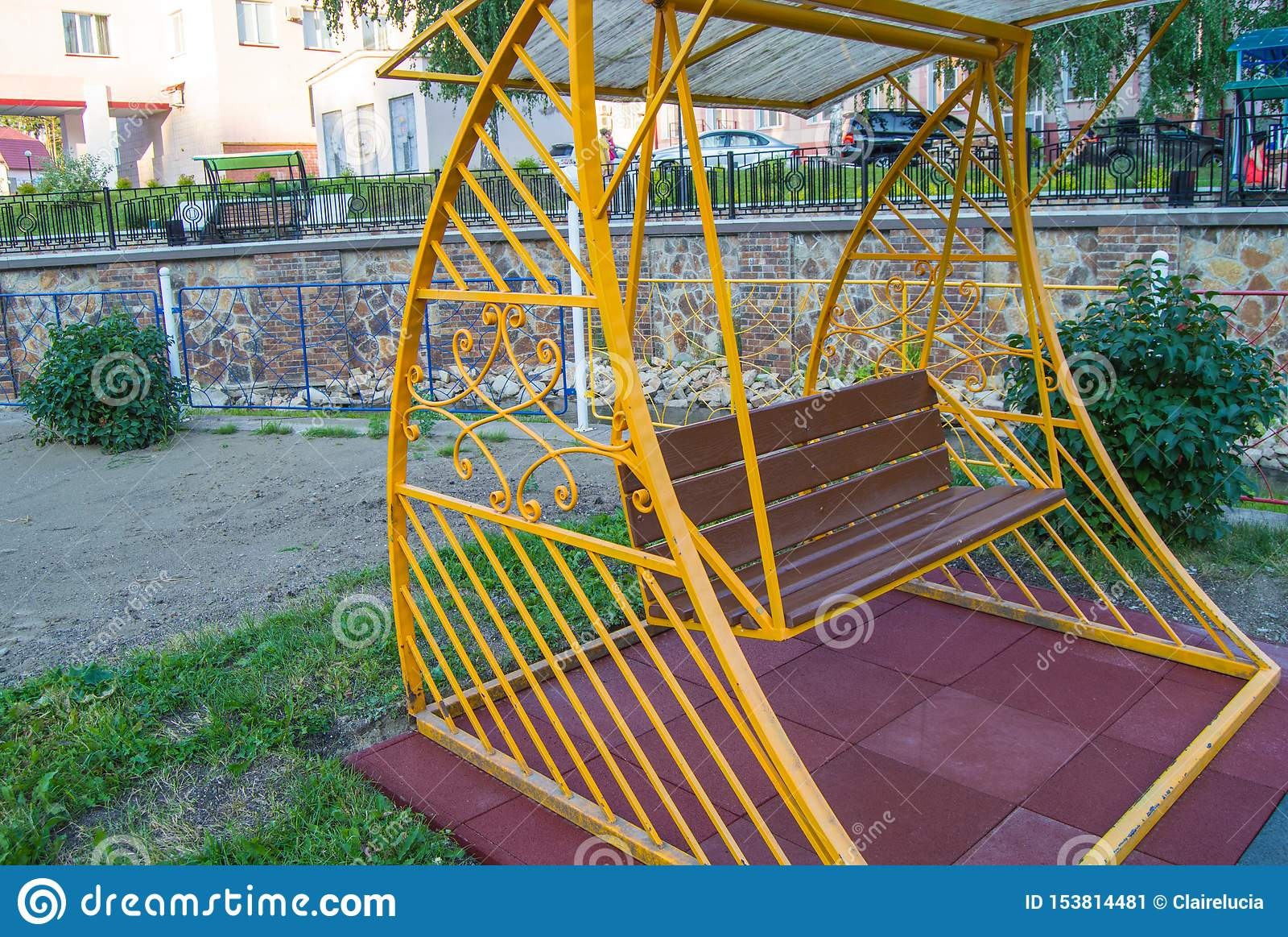 City Park in summer, empty wooden swing with yellow decorative metal frame, outdoor leisure furniture
