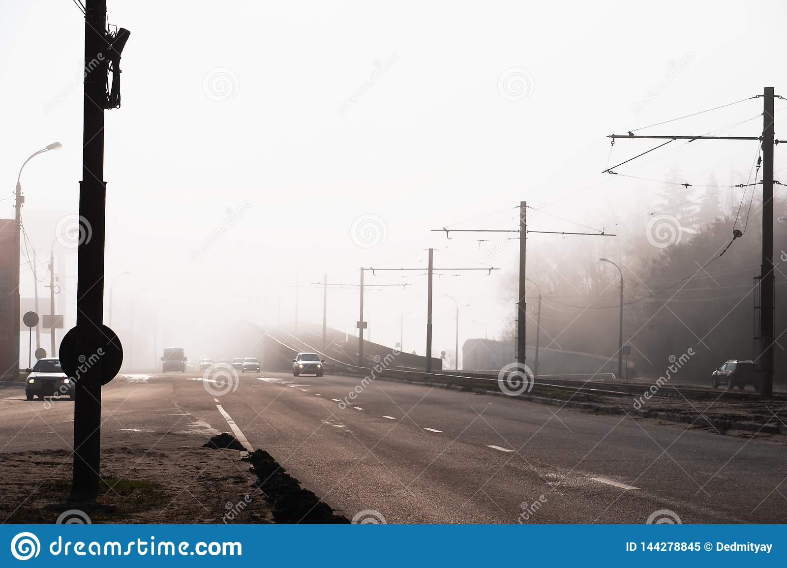City road or street with car traffic in morning spring fog or haze, atmospheric urban photo