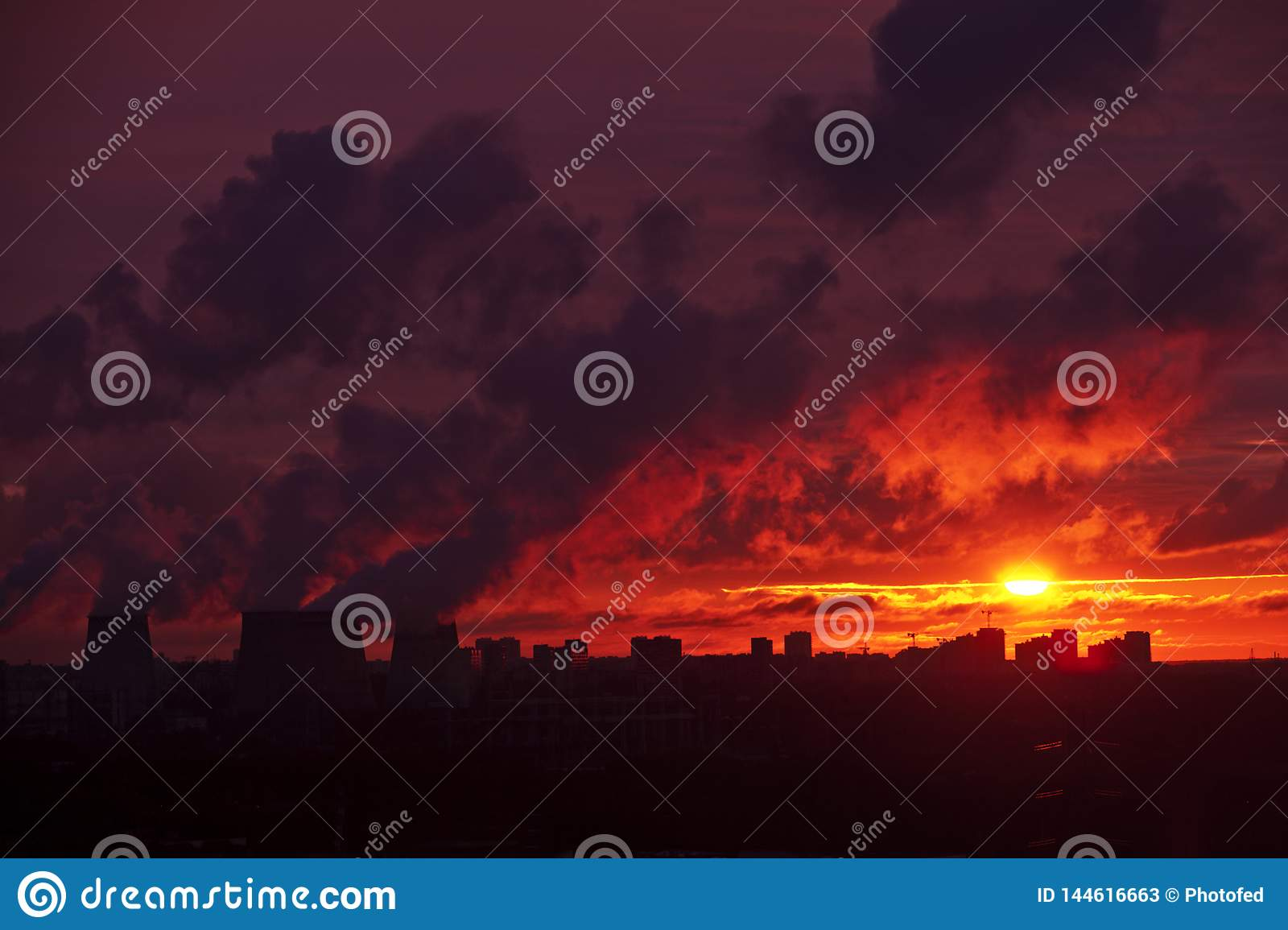 Cityscape at sunset, factory chimneys smoke, industrial landscape, night, sunset over the city