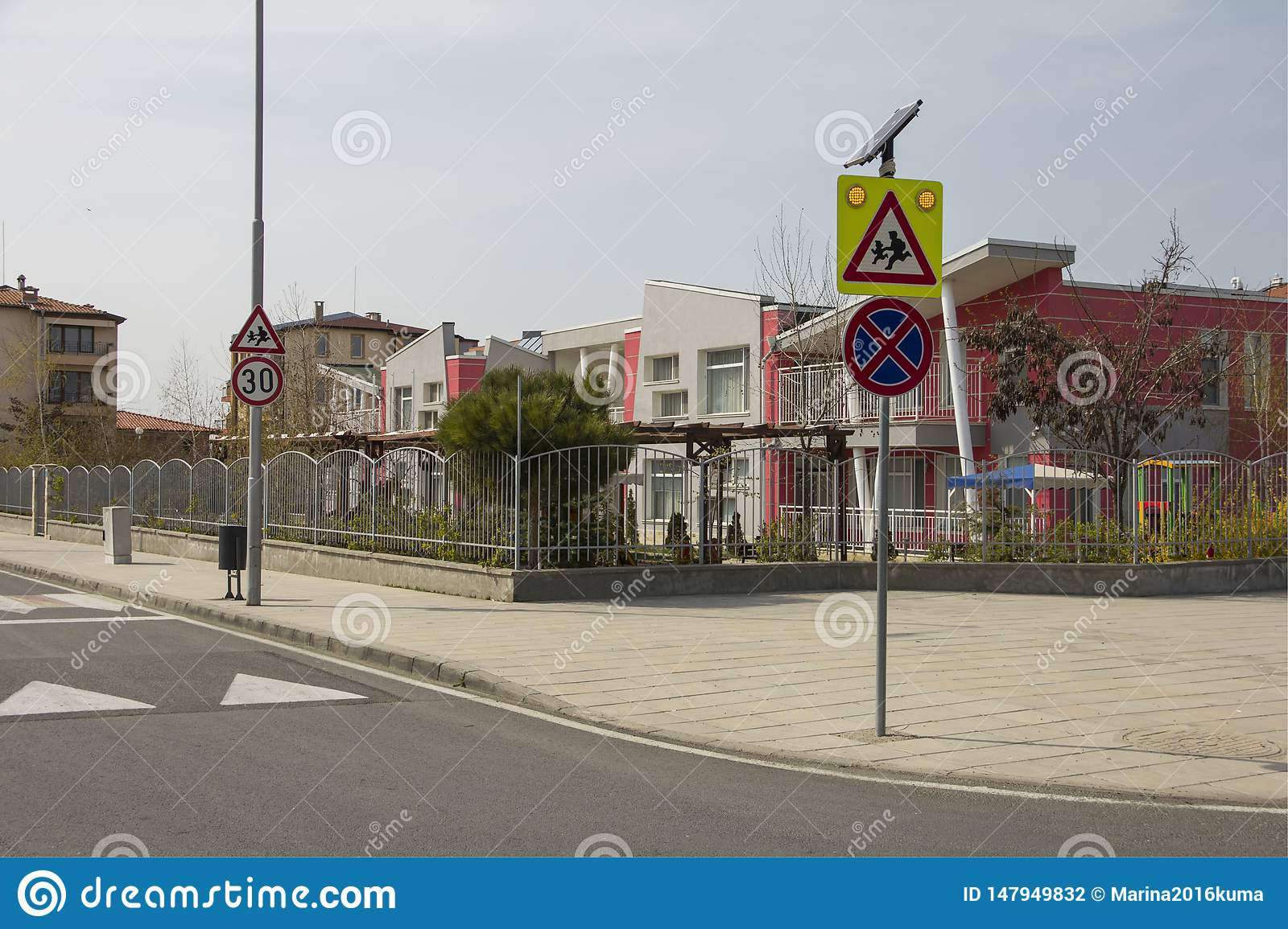 City street with a pedestrian crossing, a speed bump and a caution sign `children` near a beautiful kindergarten.