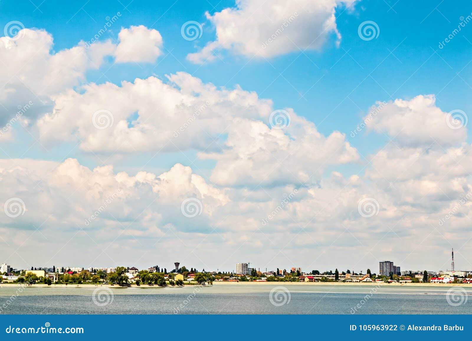 City summer landscape near lake cloudy sky