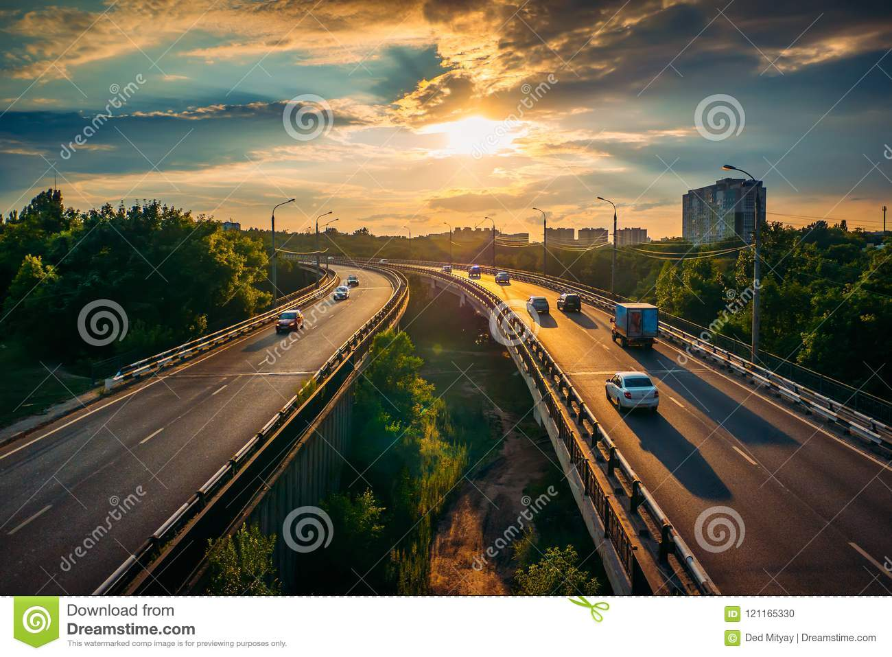 City traffic on asphalt road or highway route at sunset time, lot of cars drive with fast speed, urban transportation cityscape