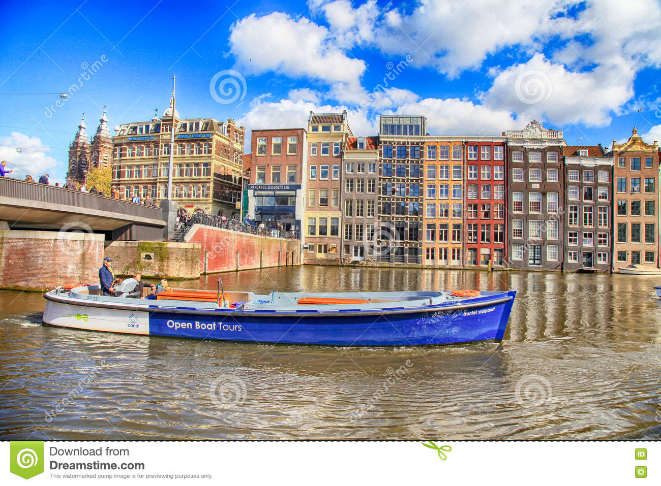 City view of canals, dutch houses and tour boat, Amsterdam, Netherlands.