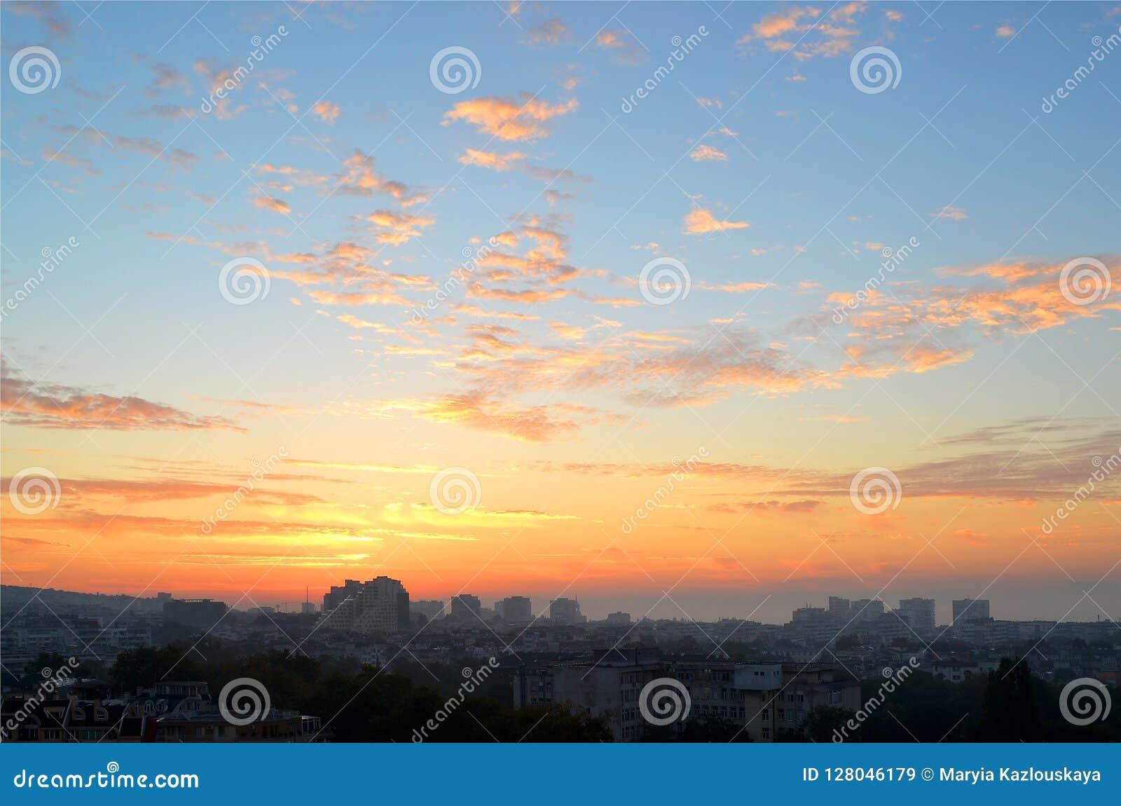 Cityscape i ottan: rosa färgen och apelsinen fördunklar på en blå himmel på gryning precis för soluppgång över den sova staden