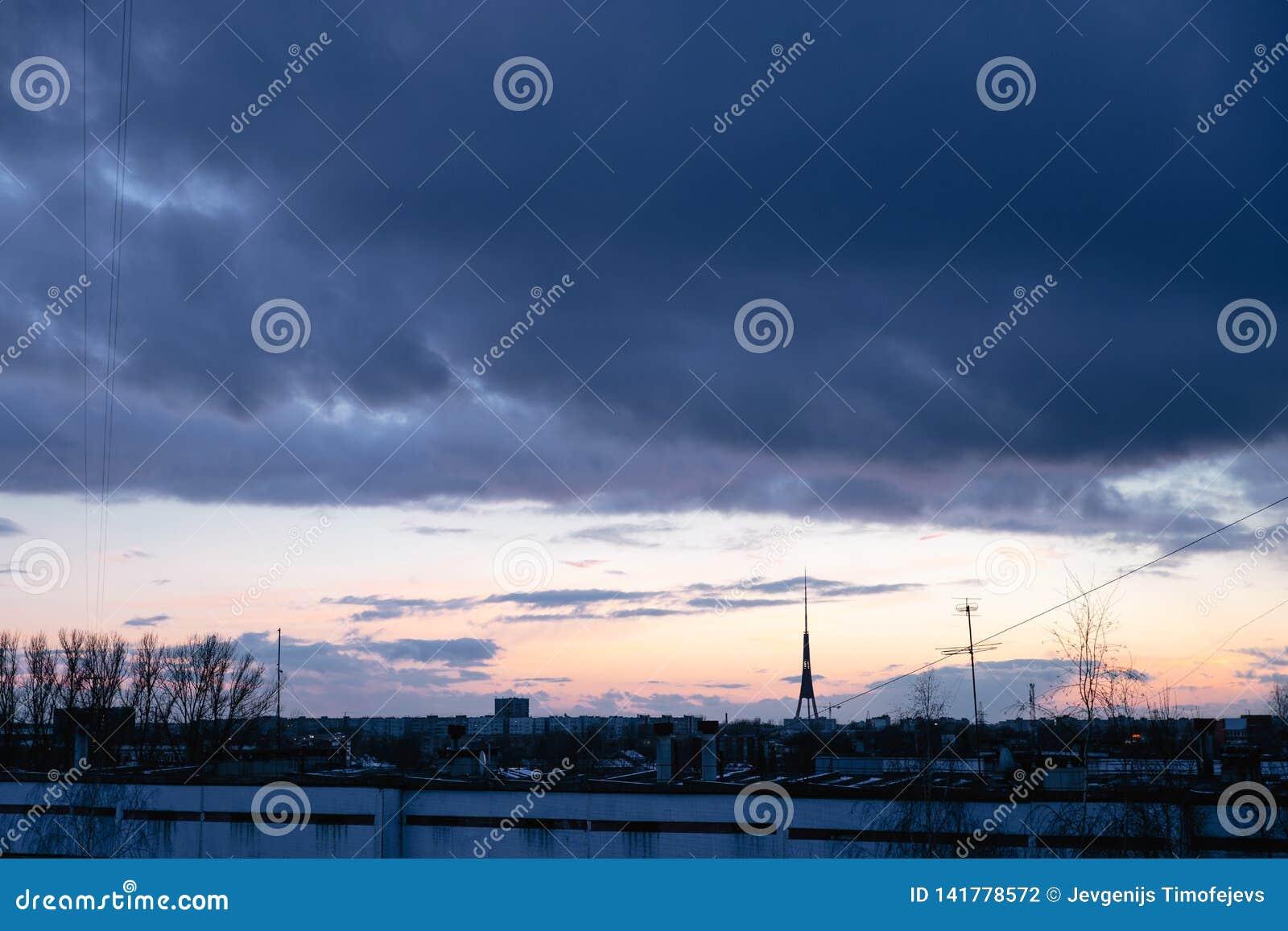 Cityscape med underbar varicolored livlig gryning Förbluffa dramatisk blå himmel med purpurfärgade och violetta moln ovanför mörk