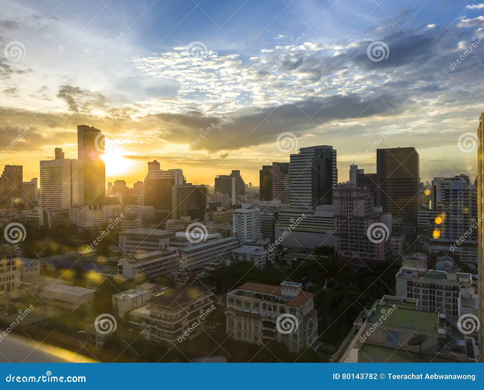 Cityscape met bokehgloed door het vensterglas met warm zonlichteffect op zonsondergangtijd leidt tot hoogtepunt en schaduw bij bu