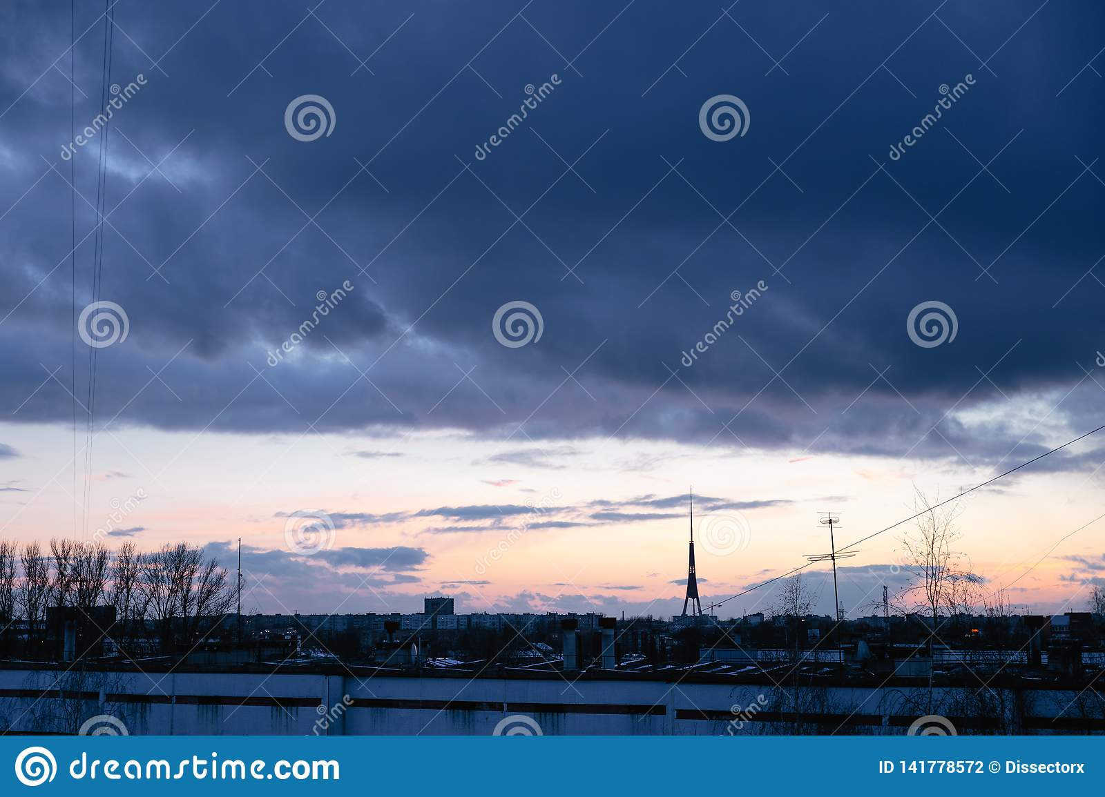 Cityscape with wonderful varicolored vivid dawn. Amazing dramatic blue sky with purple and violet clouds above dark