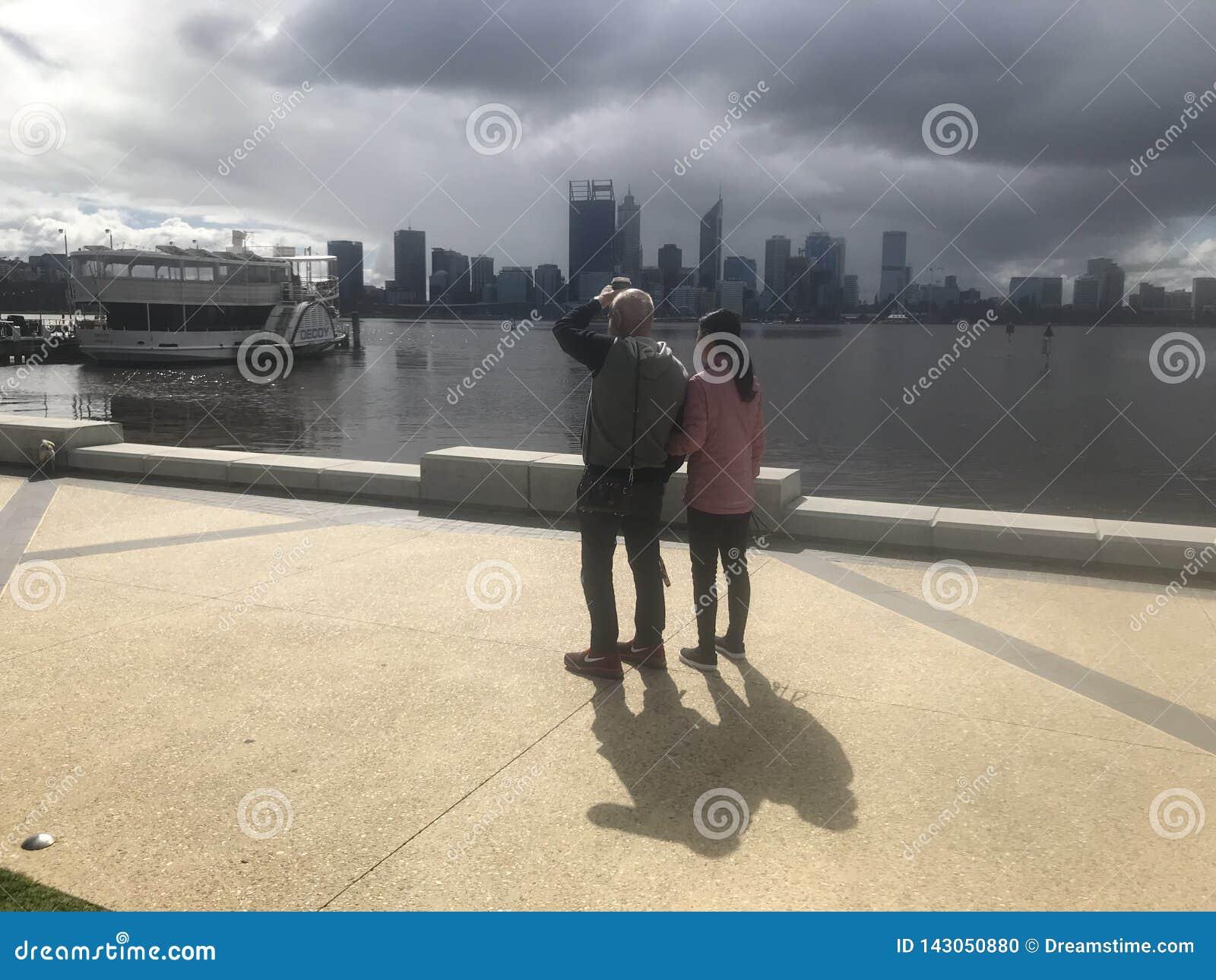 Ciudad de Perth de la tormenta que viene por el río del cisne