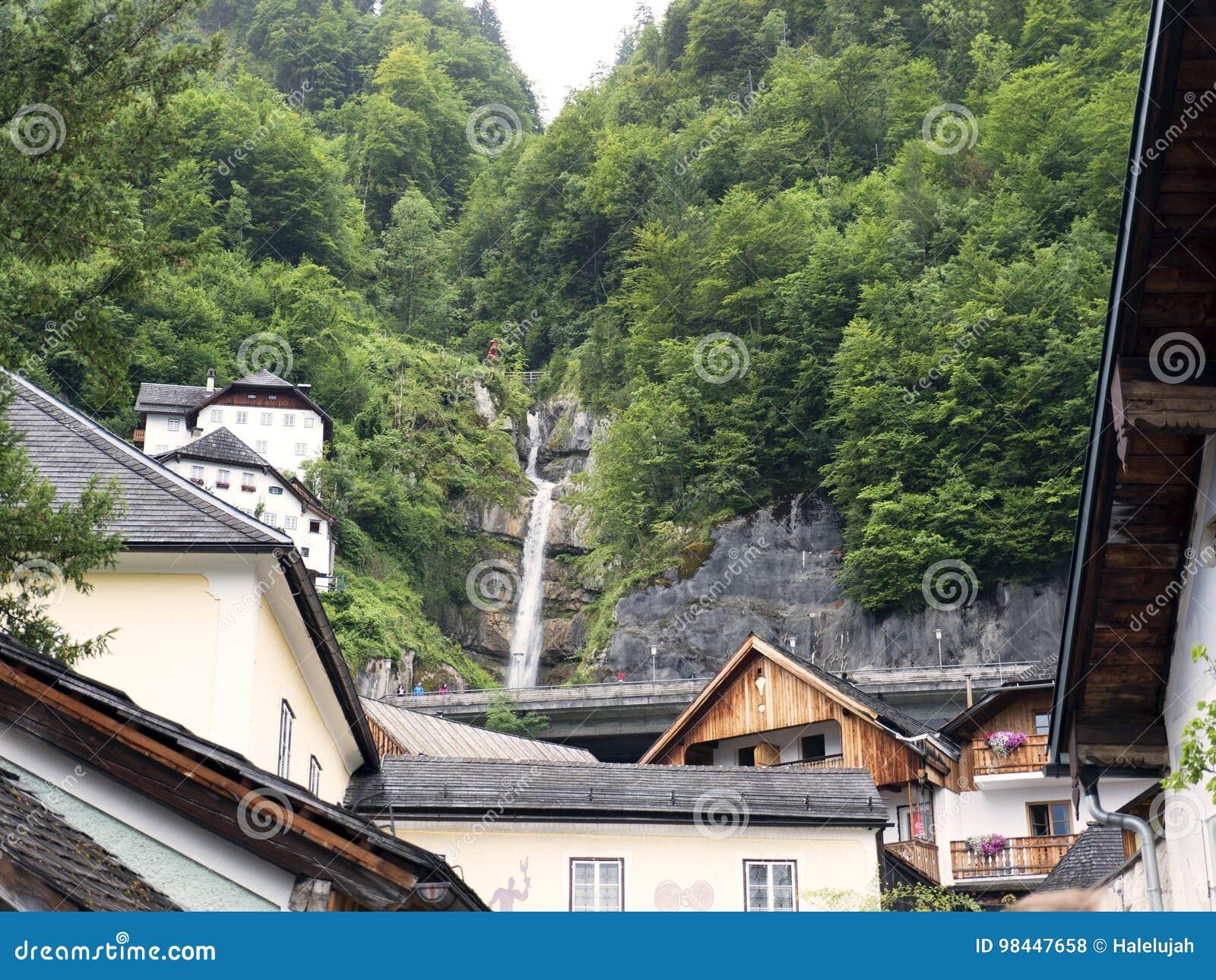 Ciudad Hallstatt con la cascada de la montaña Macizo alpino, barranco hermoso en Austria