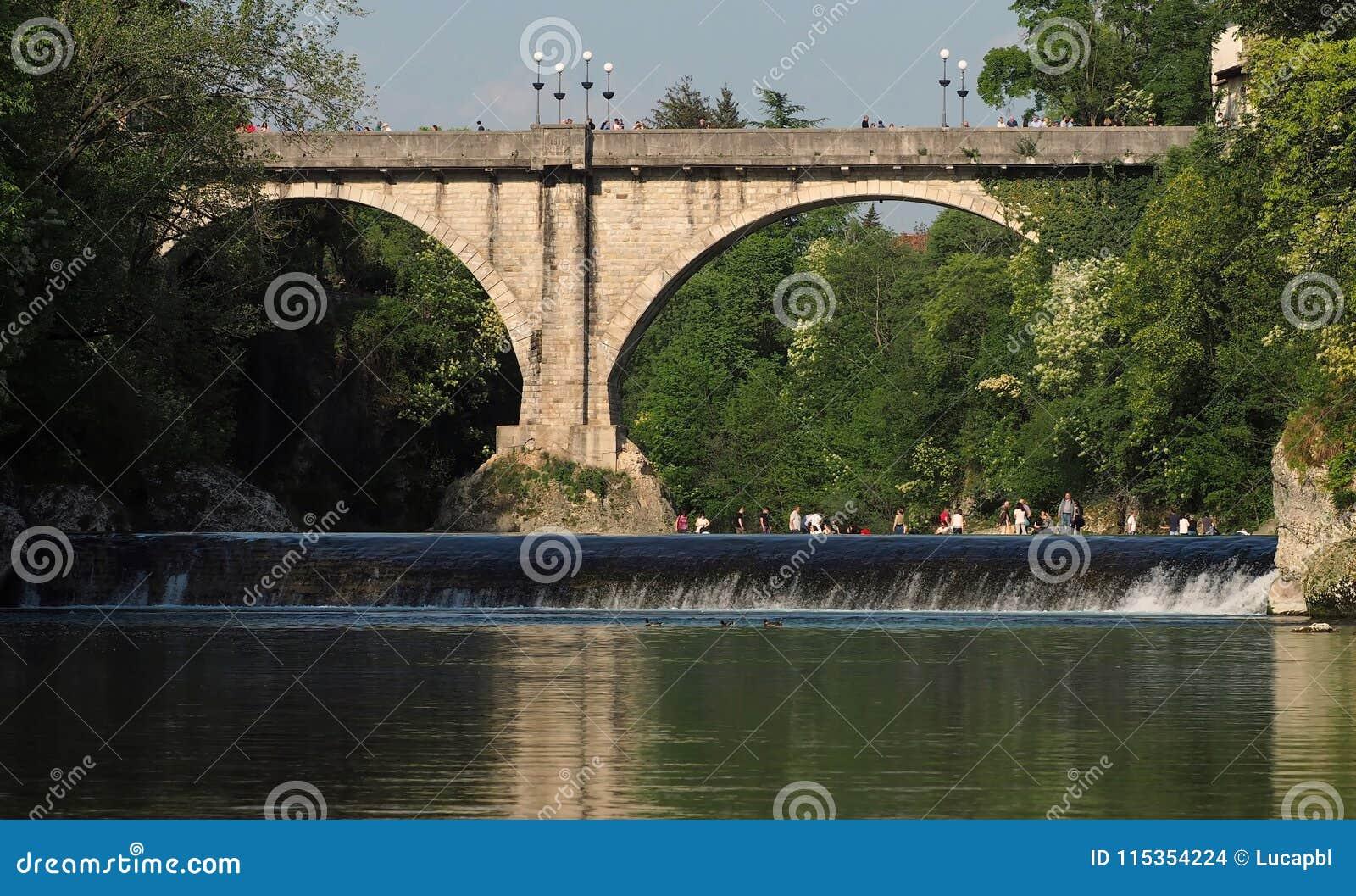 Cividale del Friuli/Italia - 25 de abril de 2018: El puente del ` s del diablo en el río de Natison con algunas personas goza del