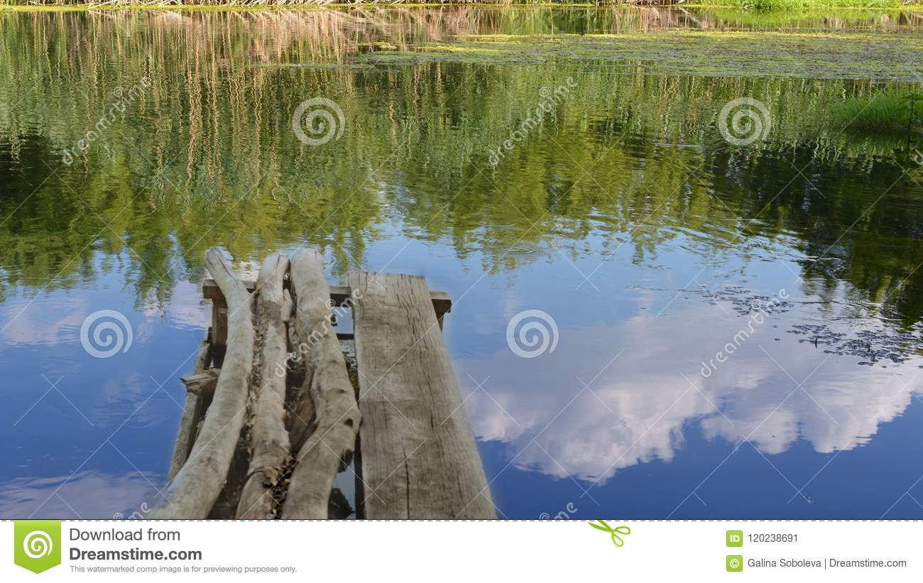 CkgroundA bridge of old beams above the river, a reflection of the blue sky and clouds