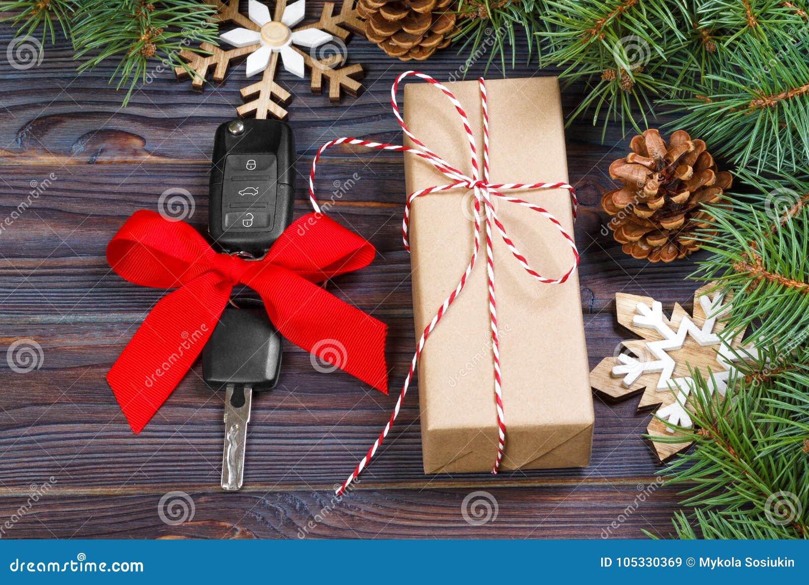 Clé de voiture avec l arc coloré avec la décoration de boîte-cadeau et de Noël sur le fond en bois