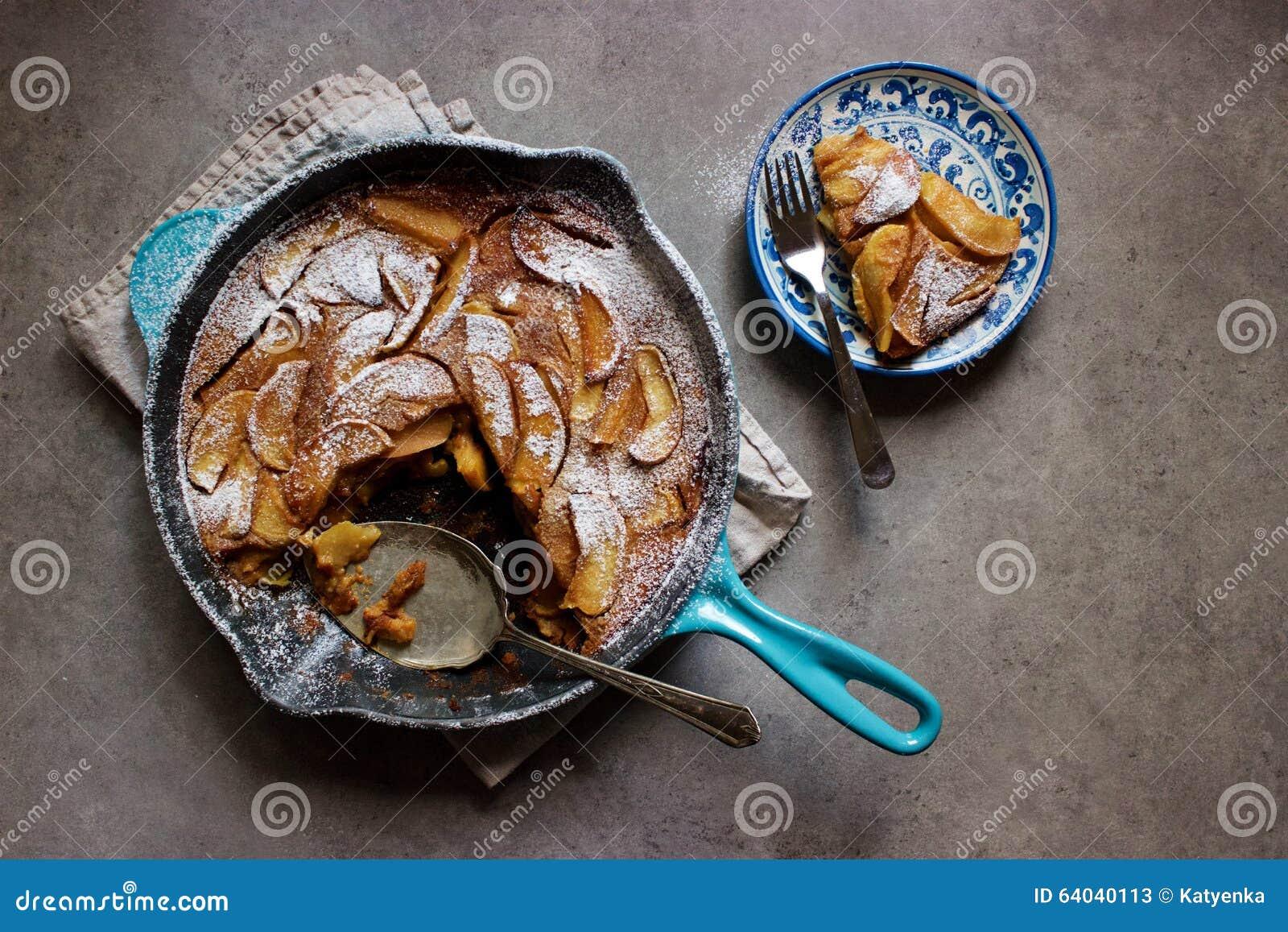 Clafoutis rôtis de pomme (gâteau français de crème anglaise) dans la casserole de fonte