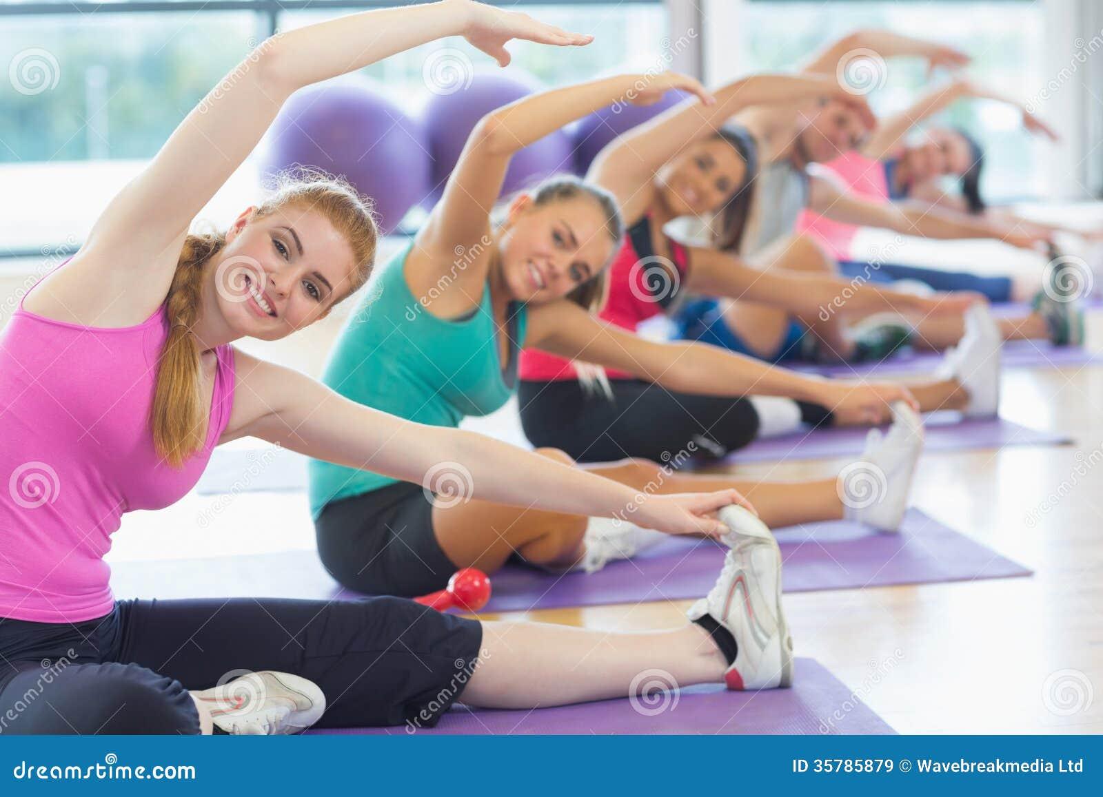 Clase e instructor de la aptitud que hacen estirando ejercicio en las esteras de la yoga