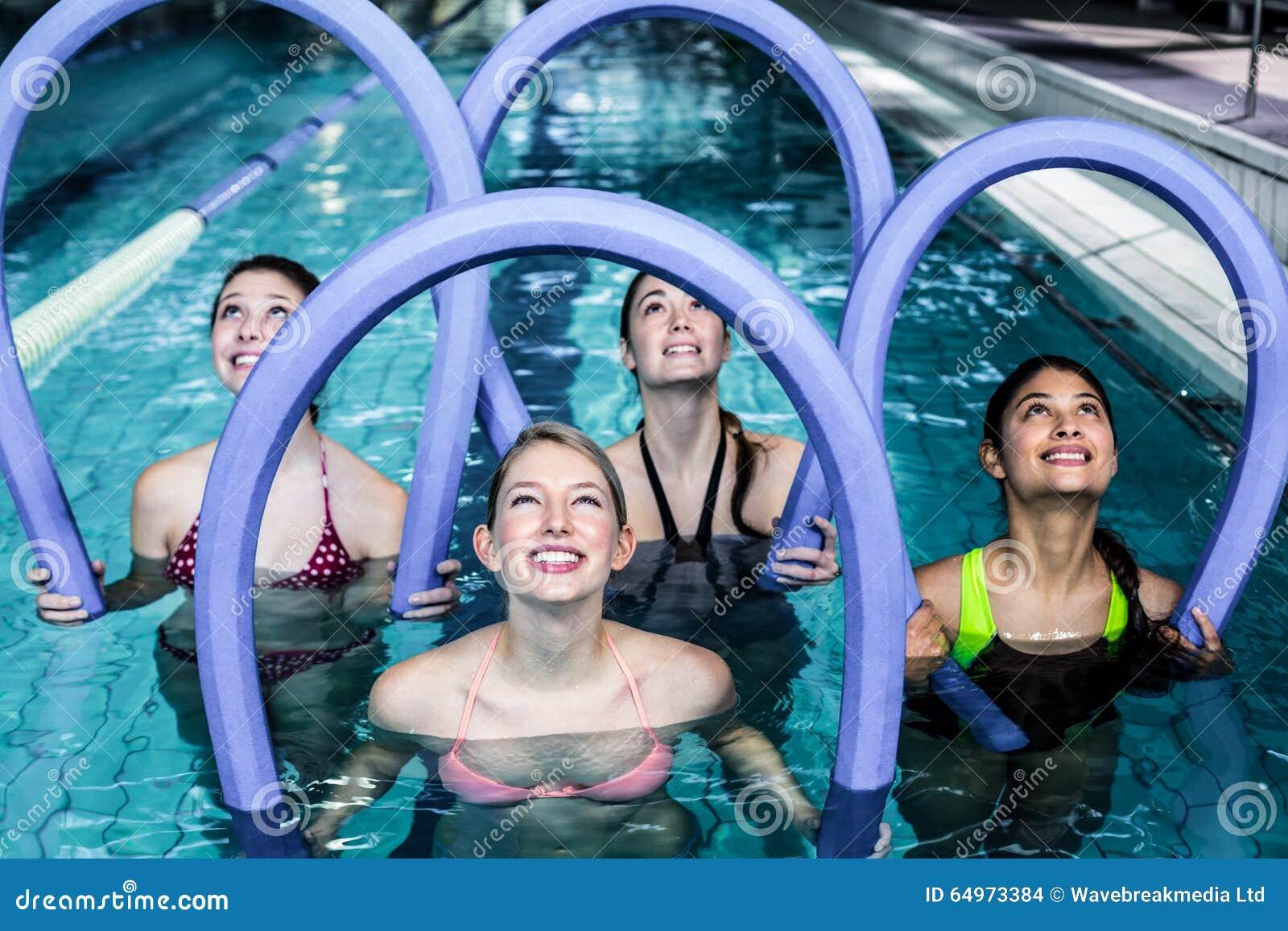 Clase feliz de la aptitud que hace aeróbicos de la aguamarina con los rodillos de la espuma