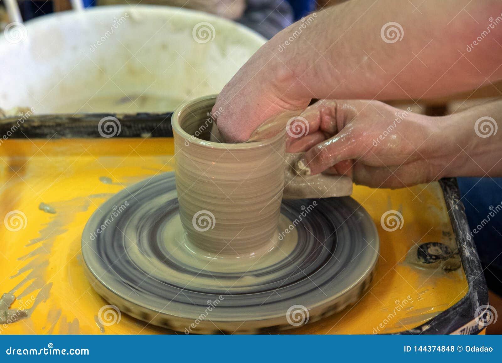 Clase principal en la fabricación de un pote de cerámica con una rueda de alfarero La cerámica está girando alrededor de su e