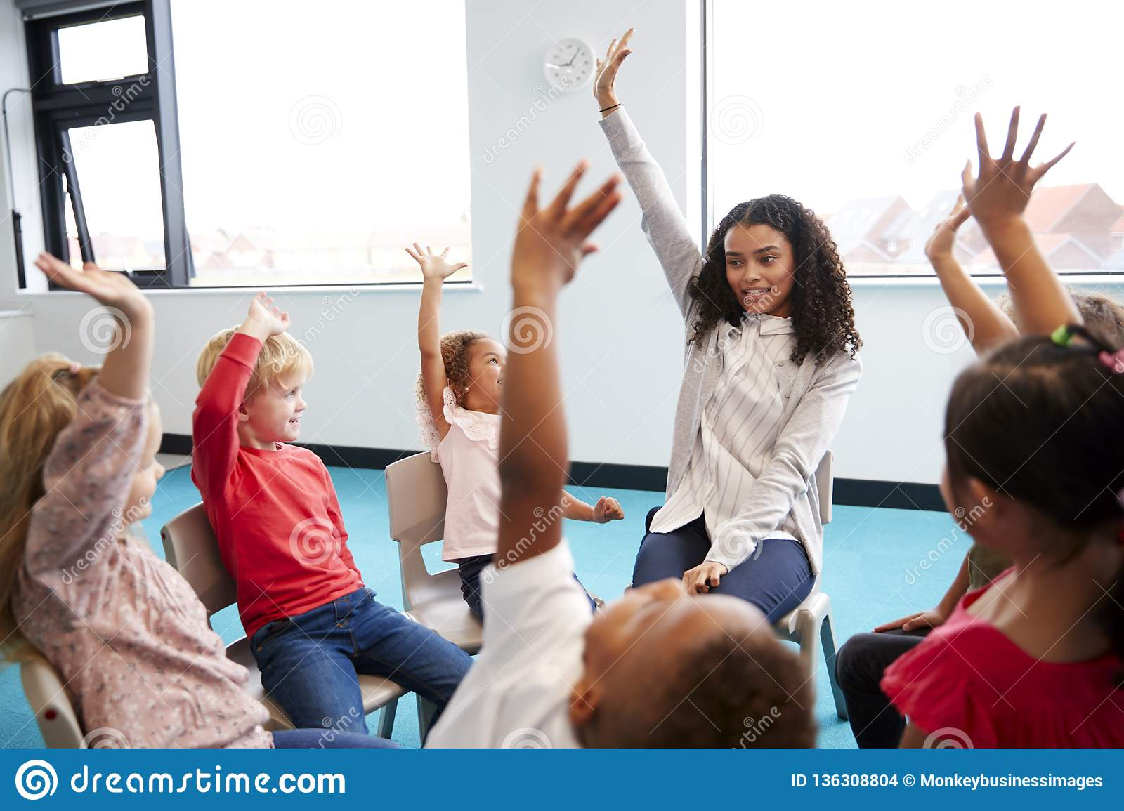 A class of infant school children sitting on chairs in a circle in the classroom, raising hands with their female teacher, close u