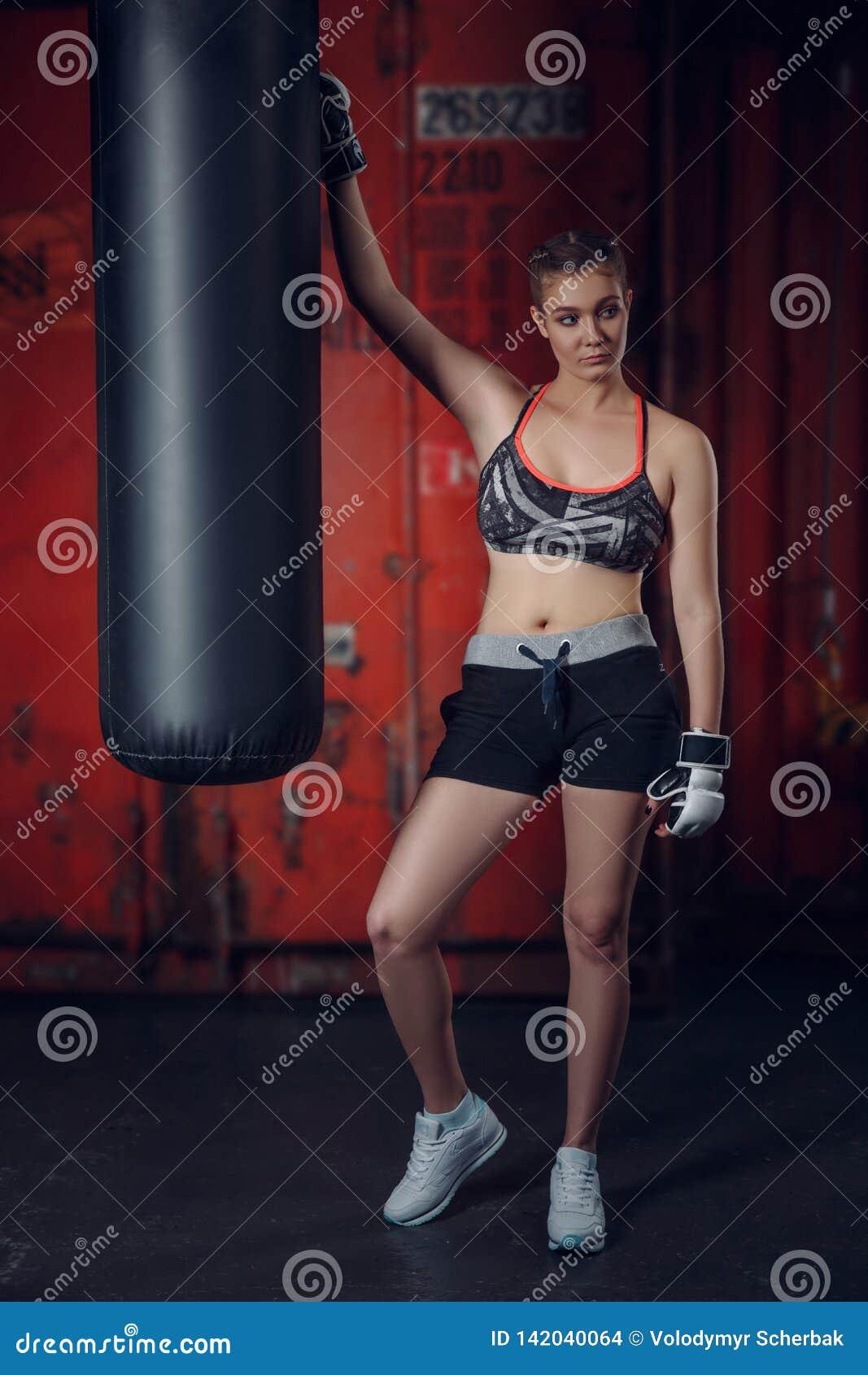 Classe de forme physique Gants de port de jeune belle femme de sports posant sur le fond du gymnase de boxe