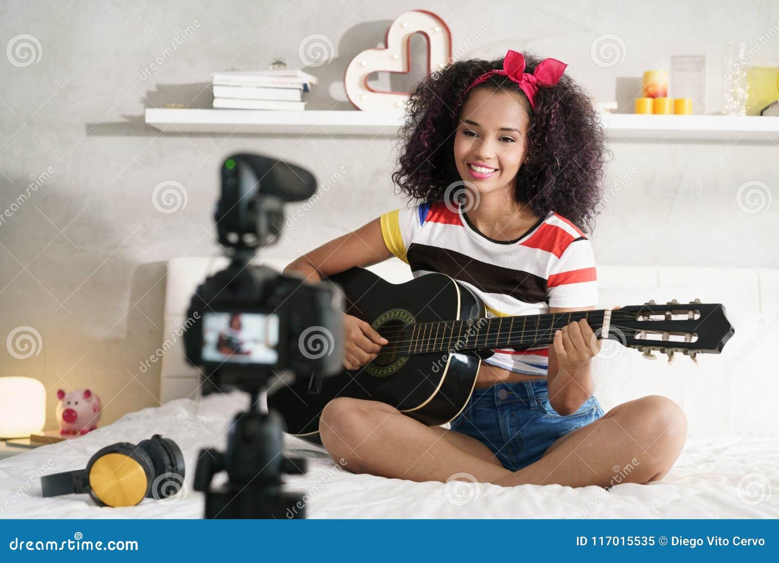 Classe de guitare de Girving de femme sur l Internet avec le cours visuel