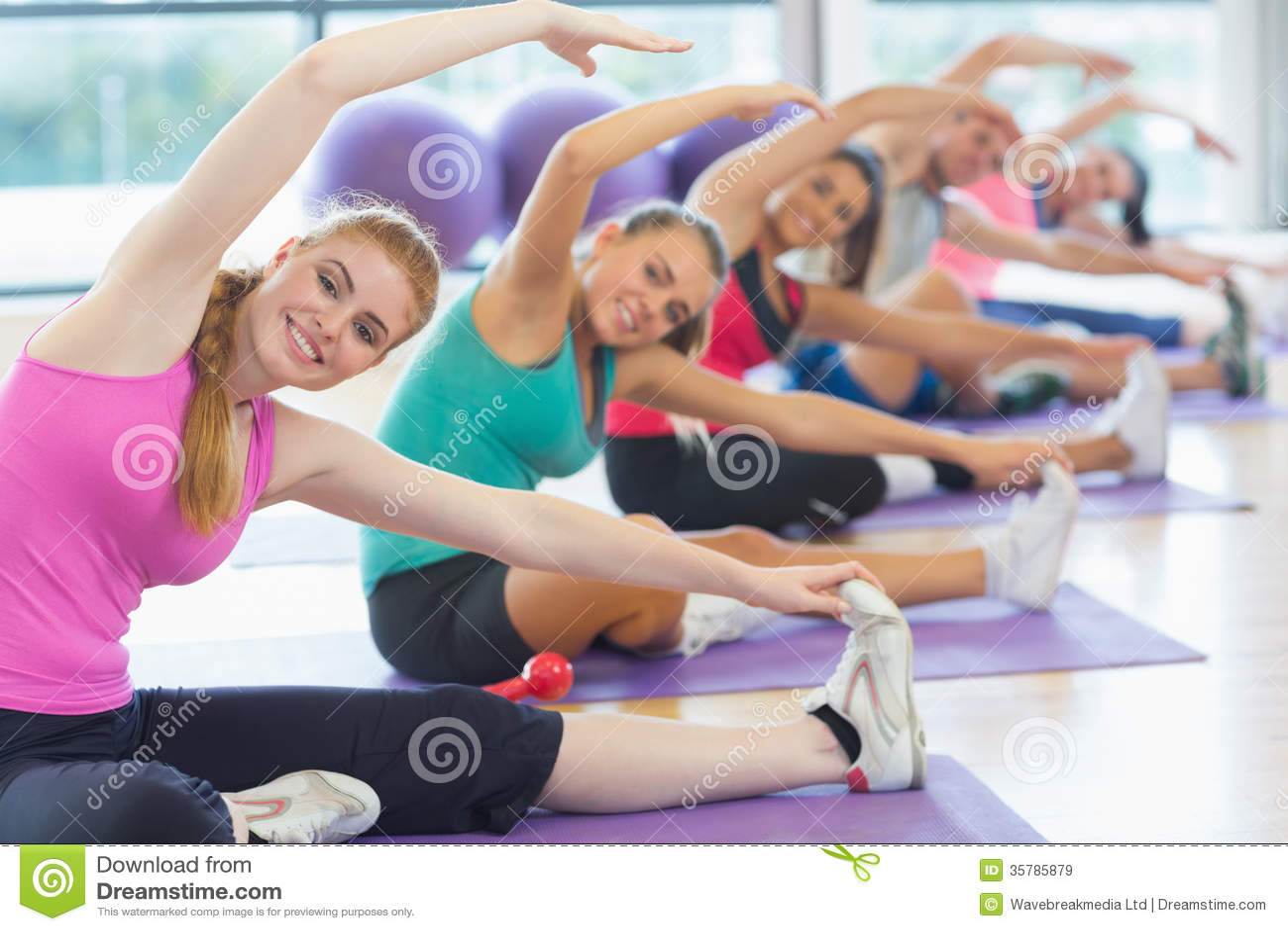 Classe et instructeur de forme physique faisant étirant l exercice sur des tapis de yoga