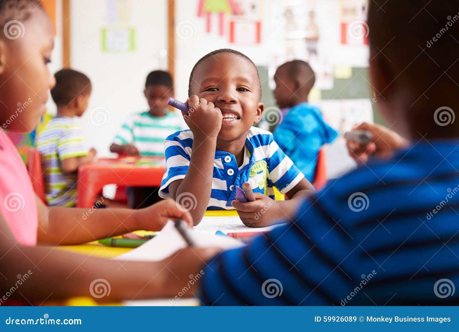 Classe prescolare nel Sudafrica, ragazzo che guarda alla macchina fotografica