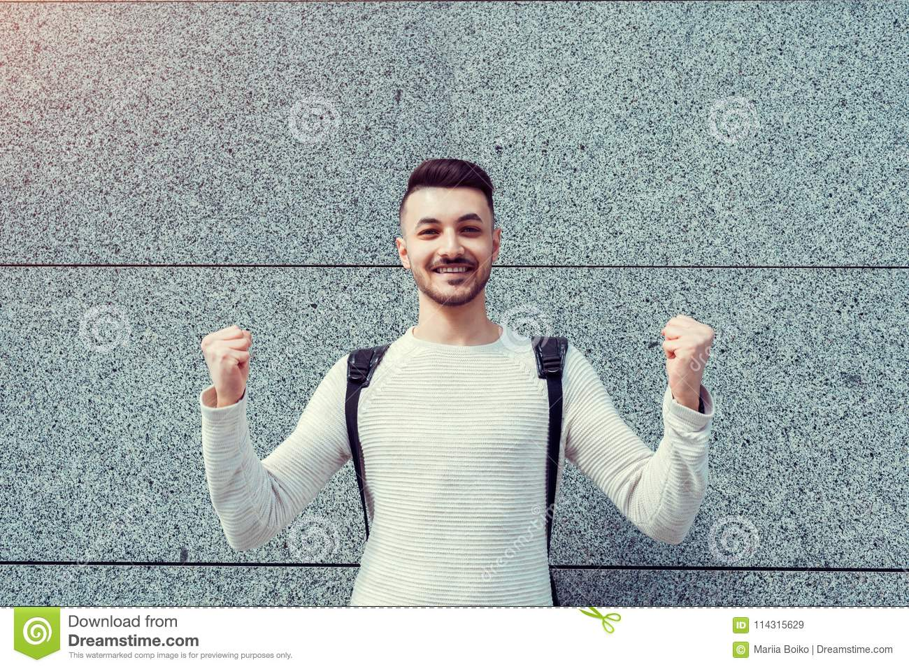 Classes canceled. Happy arabian student outside. Successful and confident young man raised hands.