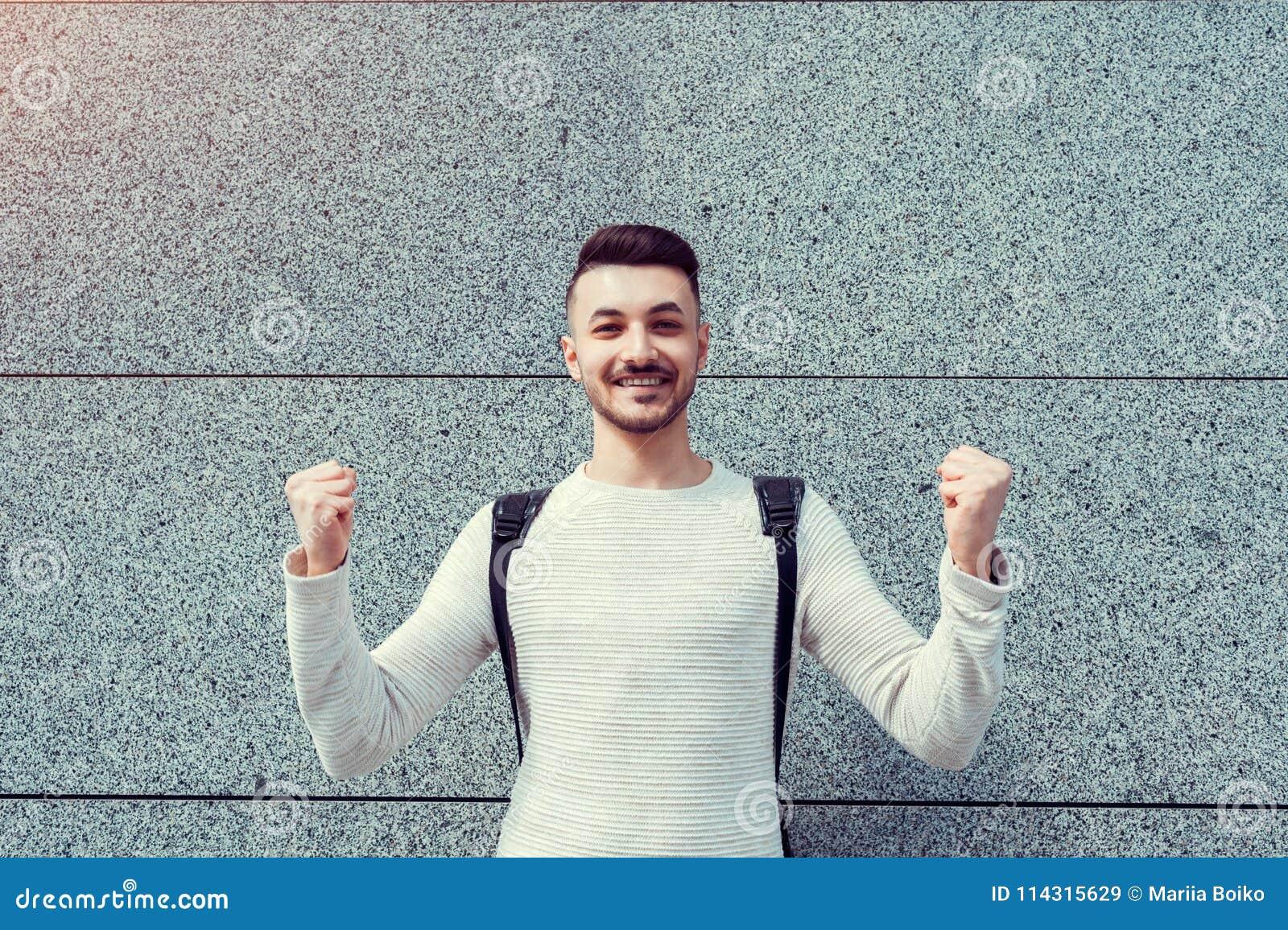 Classes décommandées Étudiant Arabe heureux dehors Et sûr mains augmentées par jeune homme réussi