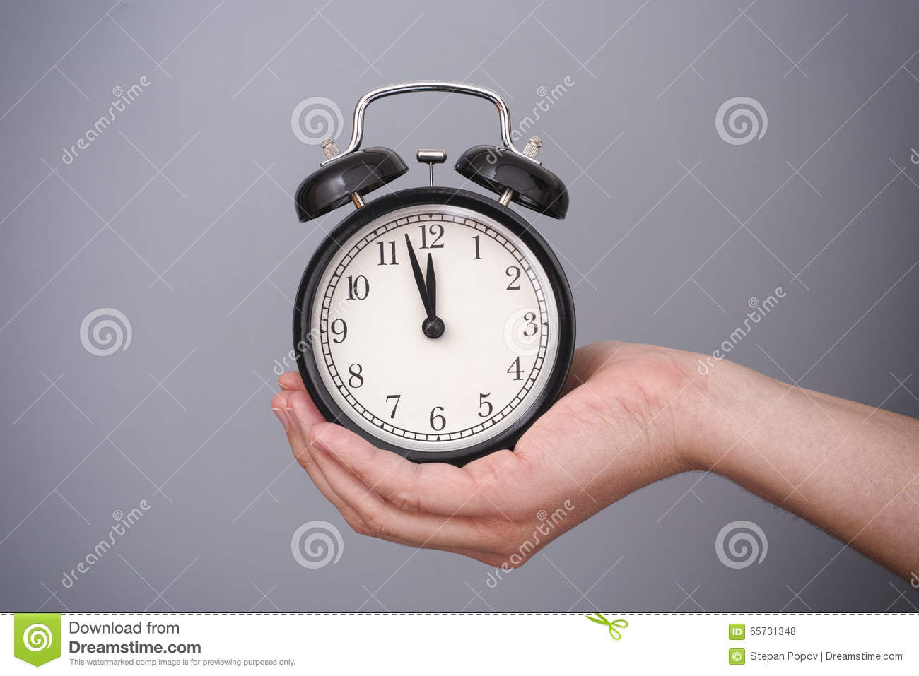 Classic Alarm Clock In Woman Hand Against Grey Background ...