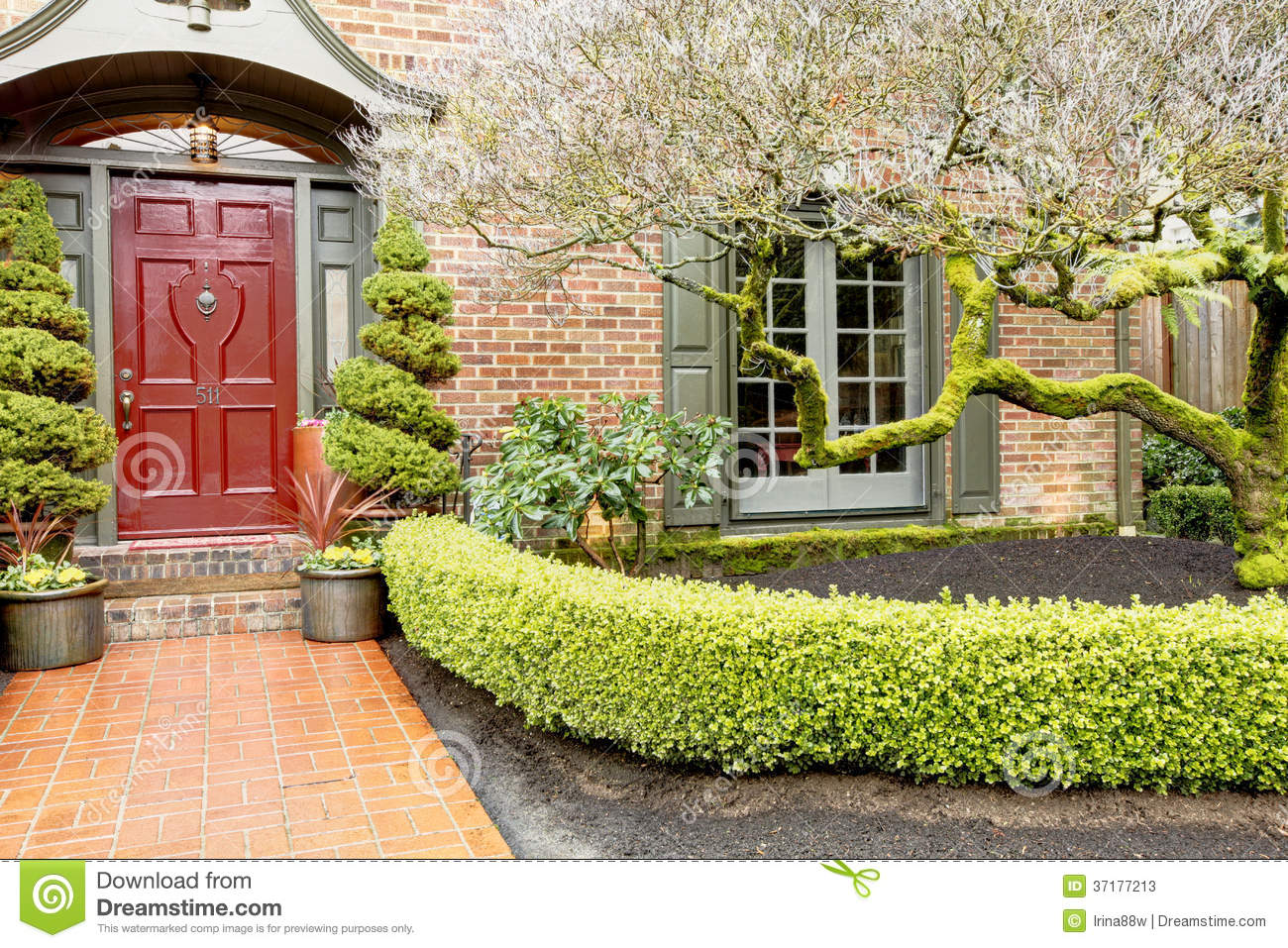 Classic brick house entrance with trim hedge stock photos Brick and wood house